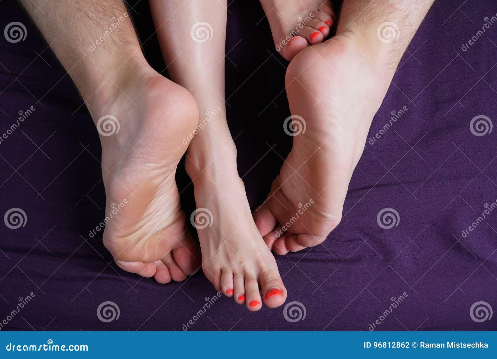 I piedi femminili e maschii si trovano su uno strato viola Gli amanti fanno sesso