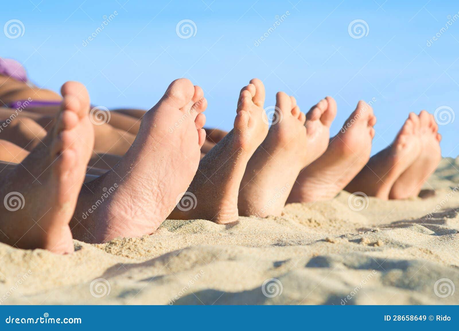 I piedi si rilassano alla spiaggia