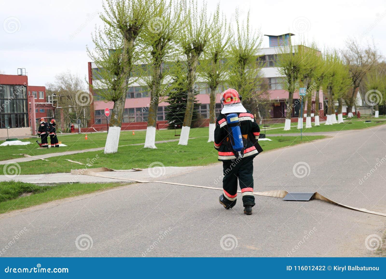 I pompieri professionisti, i soccorritori in vestiti a prova di fuoco protettivi, i caschi e le maschere antigas con le bombole d