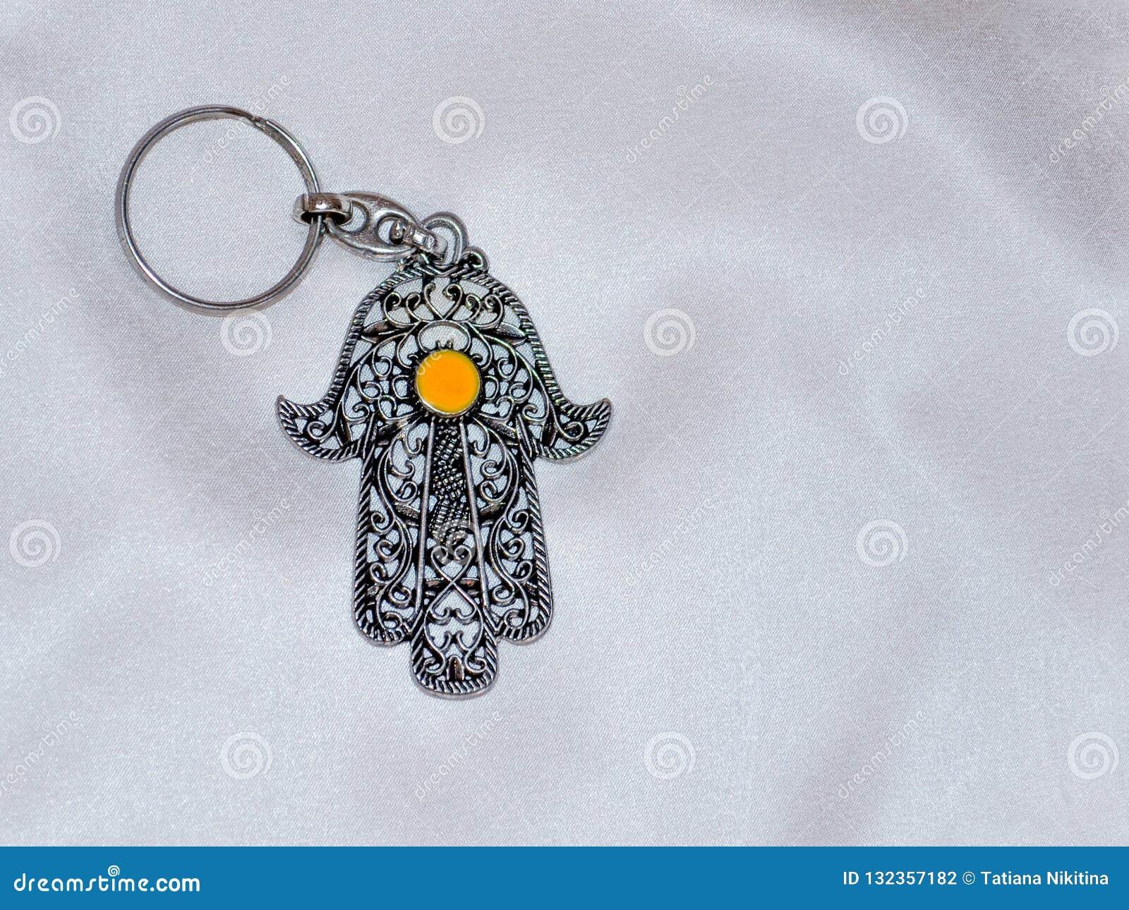I portachiavi a anello sotto forma di Fatima Hand su un fondo di seta bianco Simbolo antico e ricordo turistico moderno tradizion