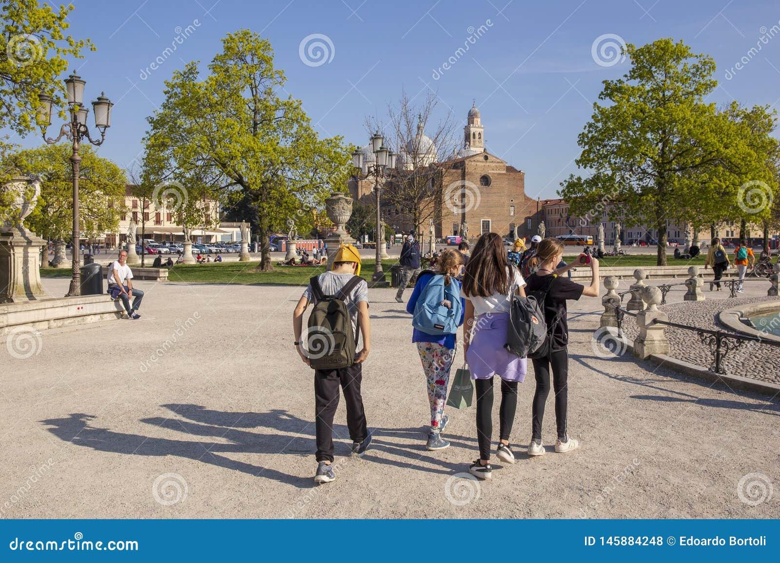 I ragazzi e le ragazze che indossano i loro zainhi stanno muovendo intorno il quadrato di Valle di della di Prato a Padova
