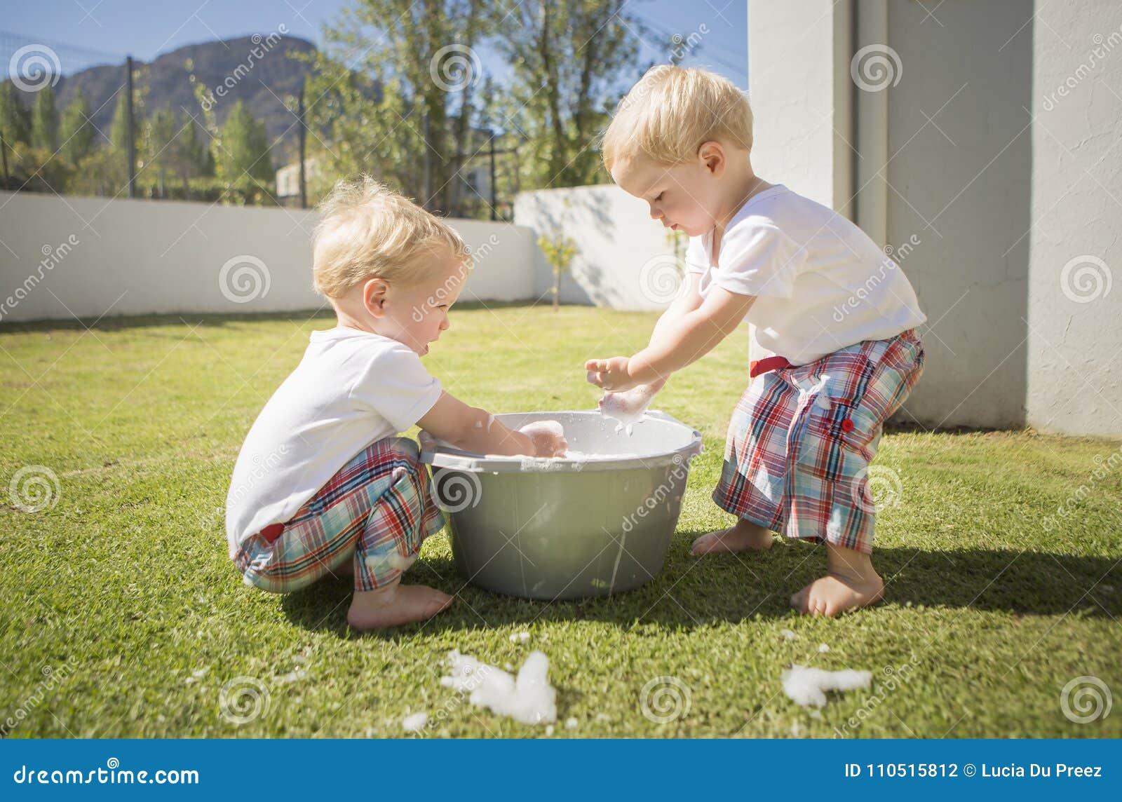 I Ragazzi Gemellati Si Lavano Le Loro Mani In Un Secchio Spumoso Su