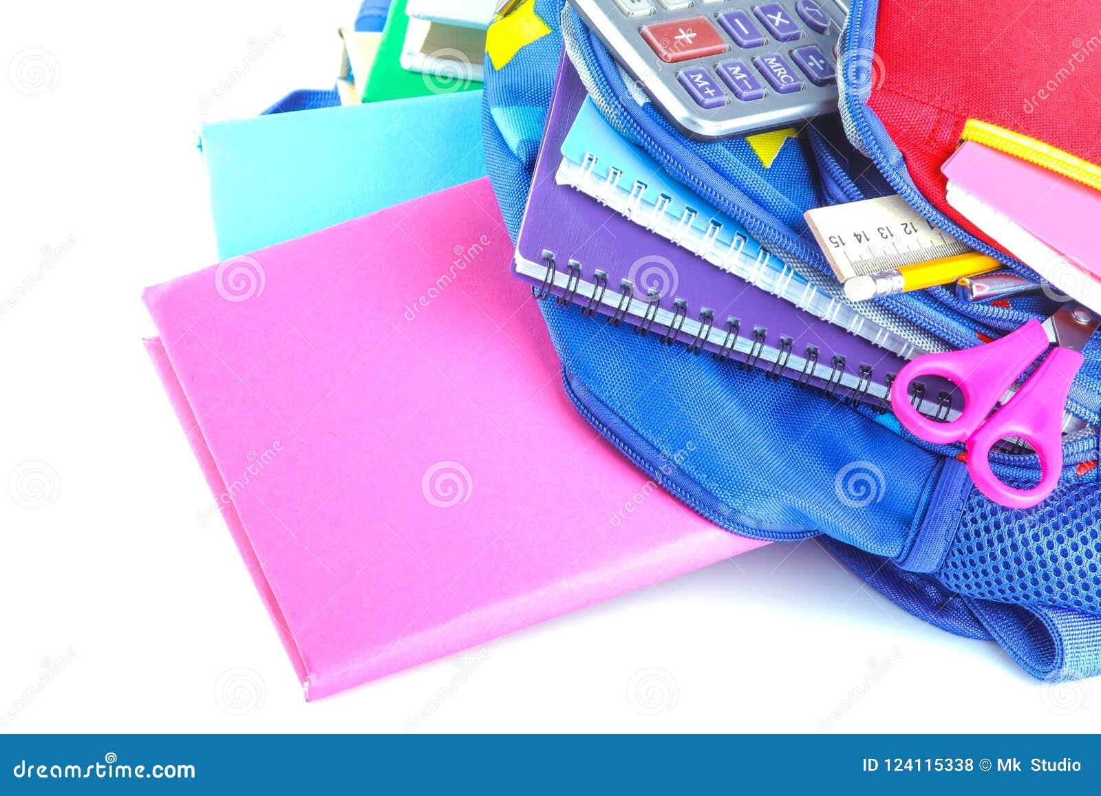 I rifornimenti differenti di scuola e della cancelleria che si trovano in una scuola backpack su un fondo isolato bianco