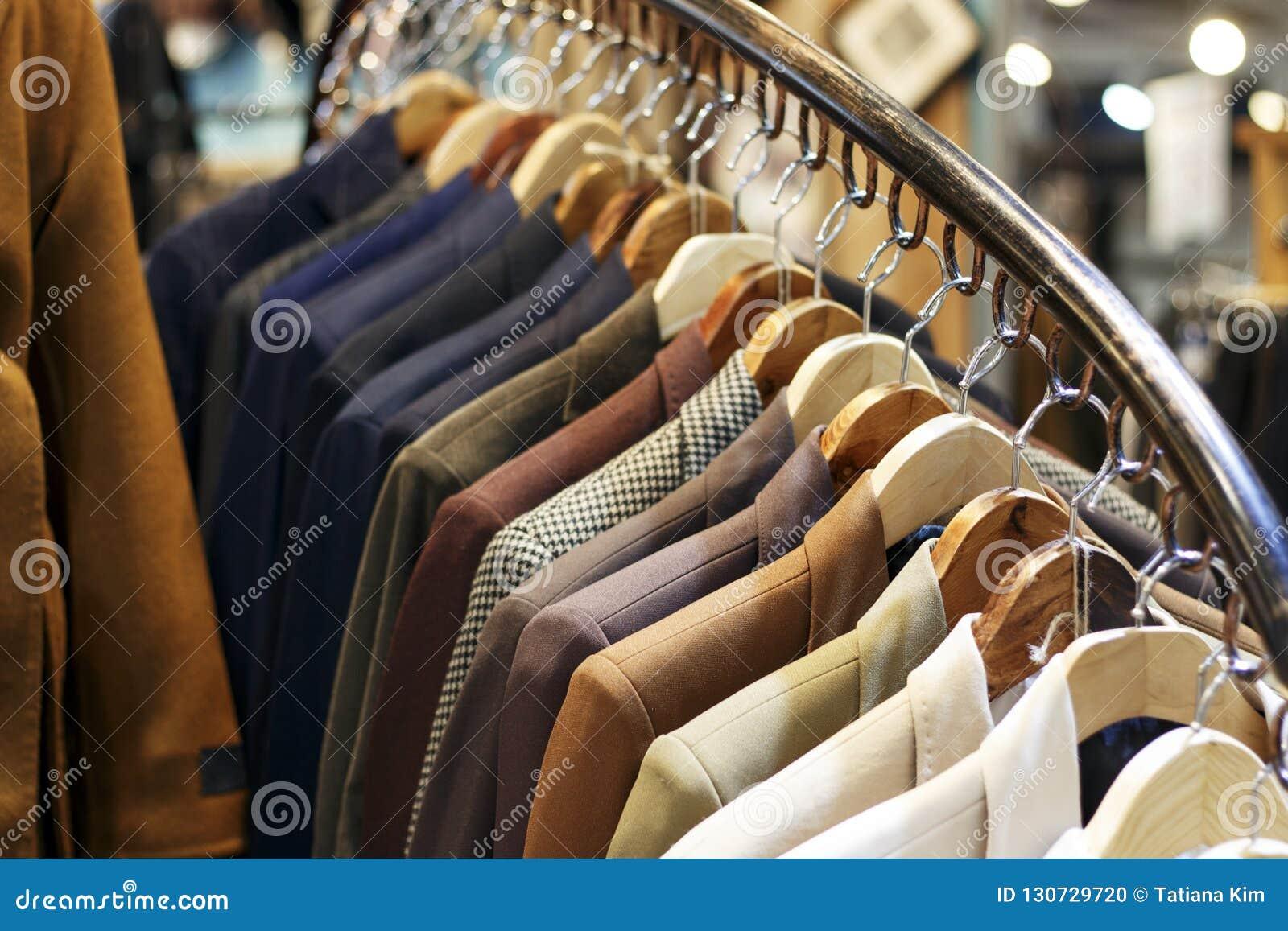I rivestimenti degli uomini alla moda sui ganci nel deposito, primo piano