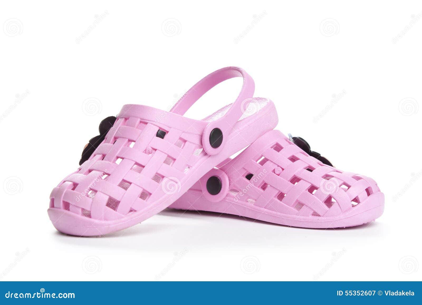 I sandali di gomma dei bambini sui precedenti bianchi