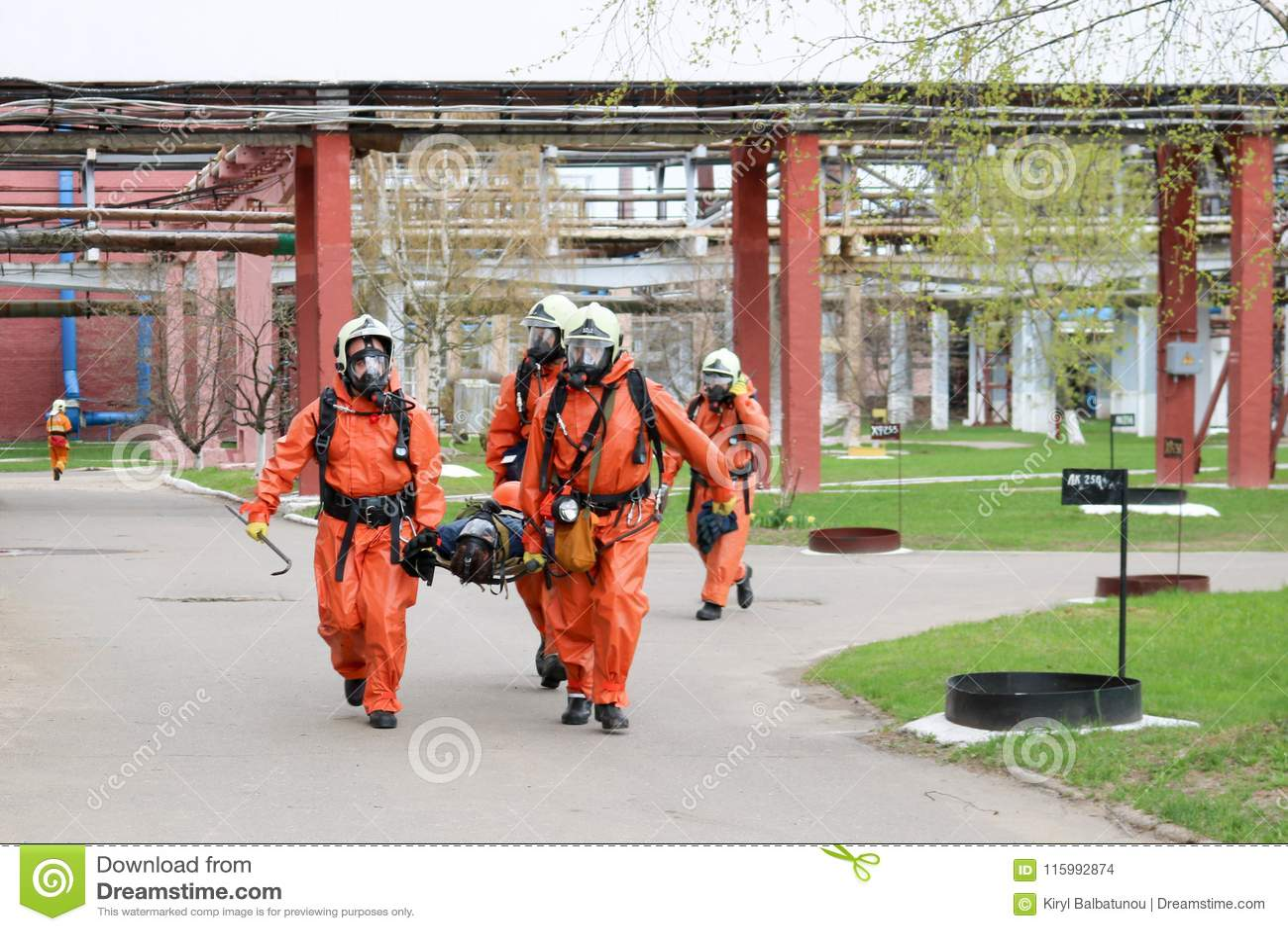 I soccorritori professionisti dei pompieri in vestiti resistenti al fuoco protettivi arancio, caschi bianchi e maschere antigas s