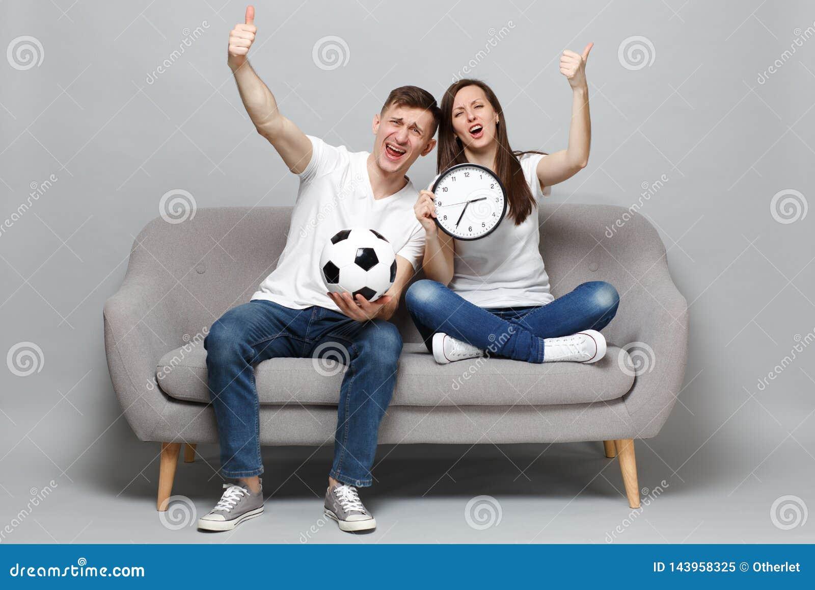 I tifosi dell uomo della donna delle coppie di divertimento incoraggiano sul gruppo favorito di sostegno con pallone da calcio, t