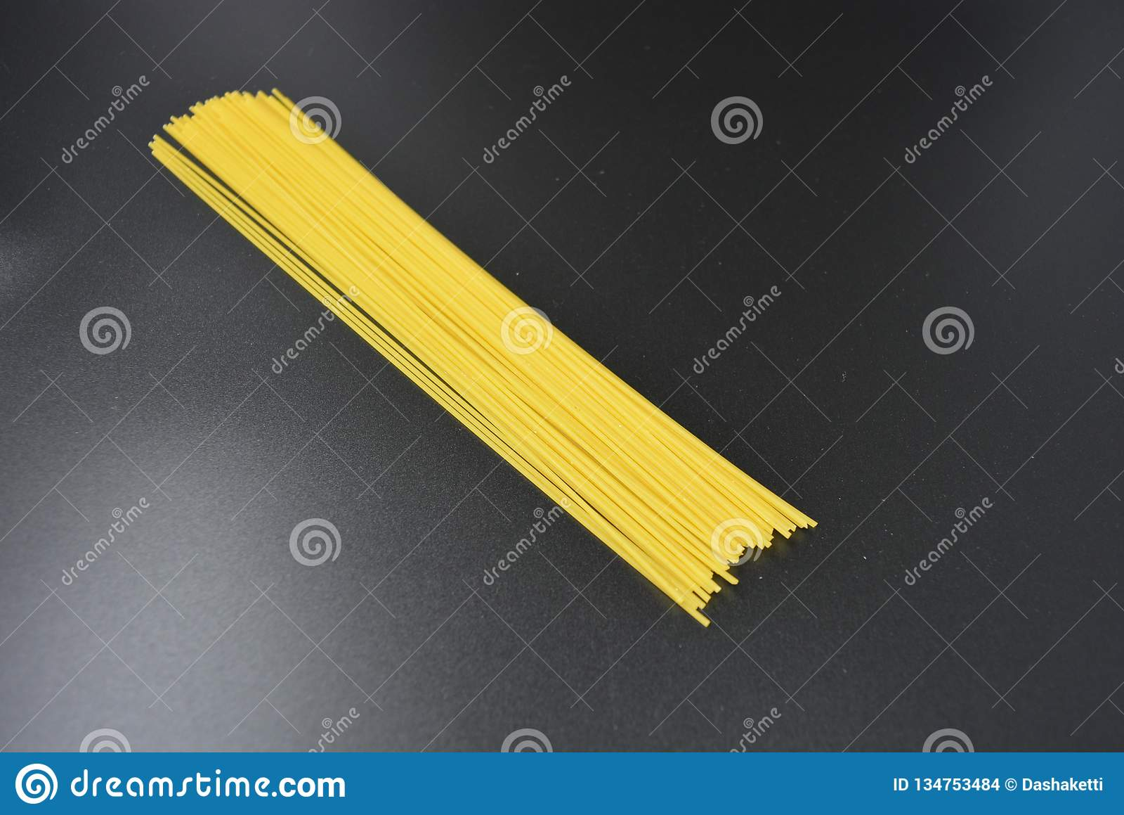 I vermicelli asciutti lunghi, spaghetti italiani della pasta dalle varietà del grano duro dentro ingrassano un fondo nero interes