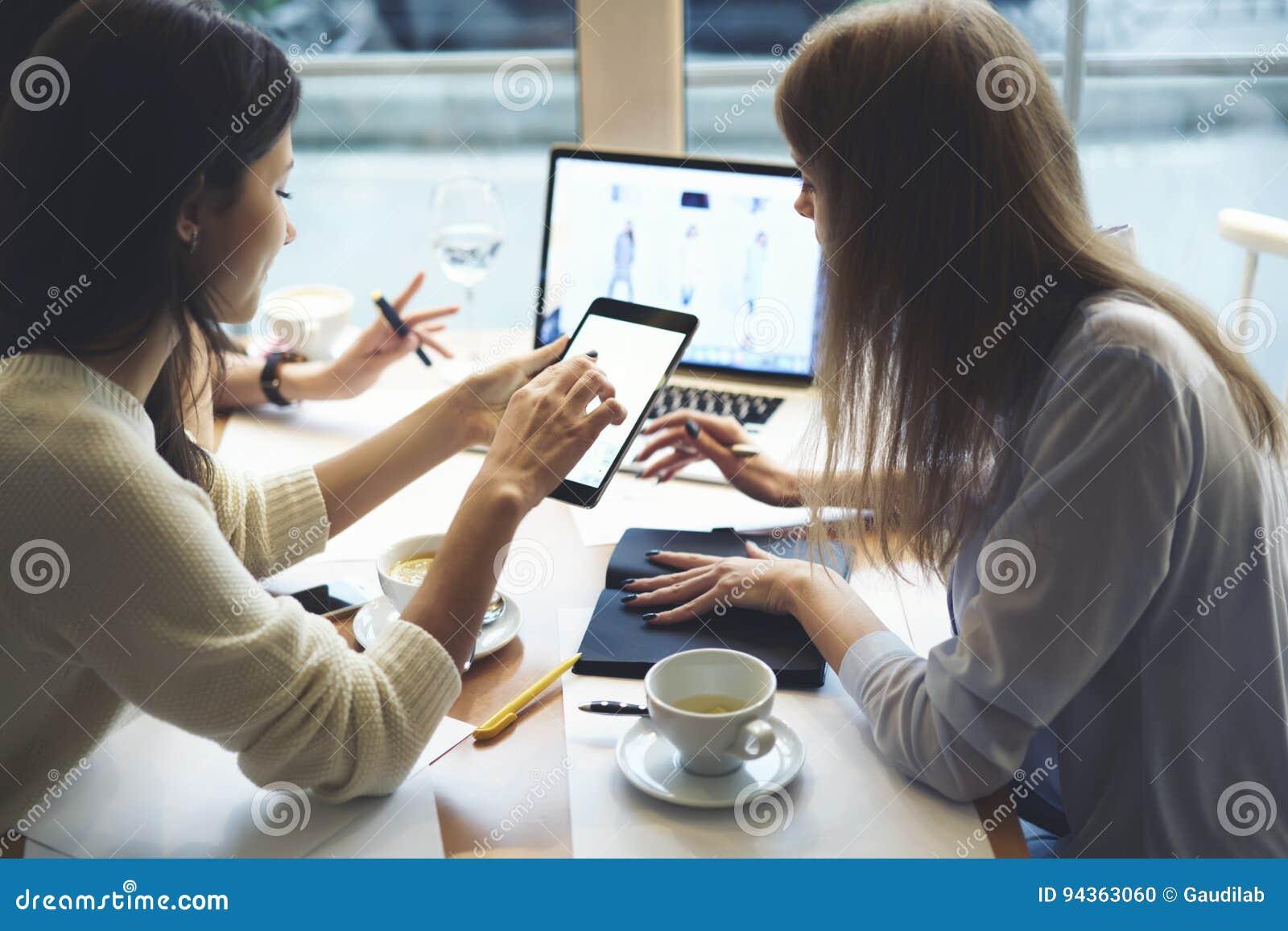 42b0276ace2d I vestiti di progettisti delle ragazze che funzionano insieme i dispositivi  igital con derisione sullo schermo. Download preview. Salva in ...