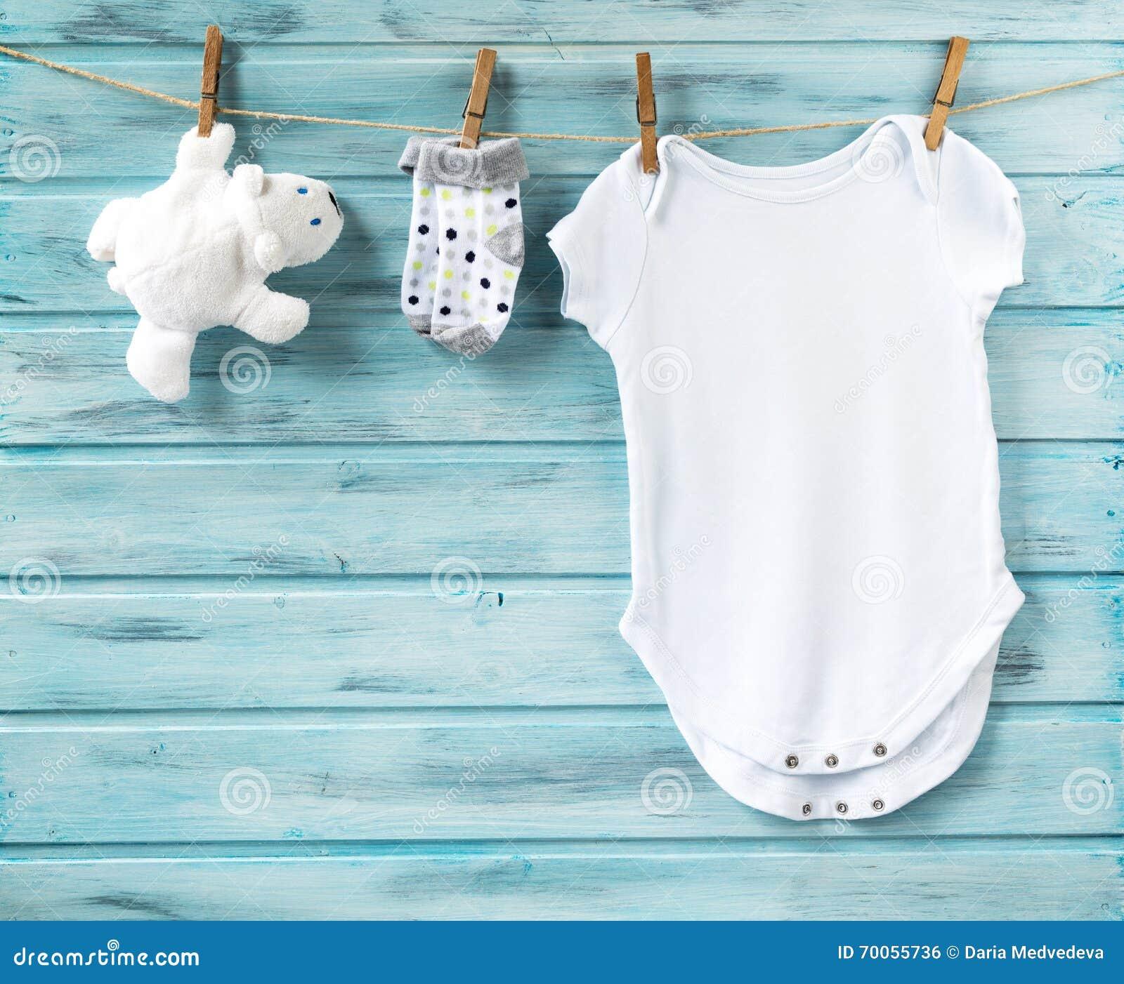 I vestiti e l orso bianco del neonato giocano su una corda da bucato