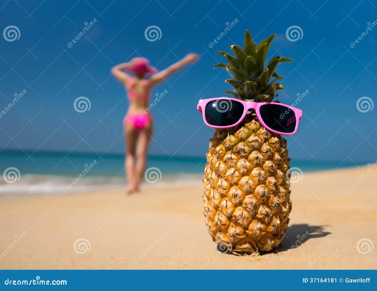 I vetri allegri dell ananas e una donna in un bikini che prende il sole sulla spiaggia sul backgrounde del mare tirano sul fondo d