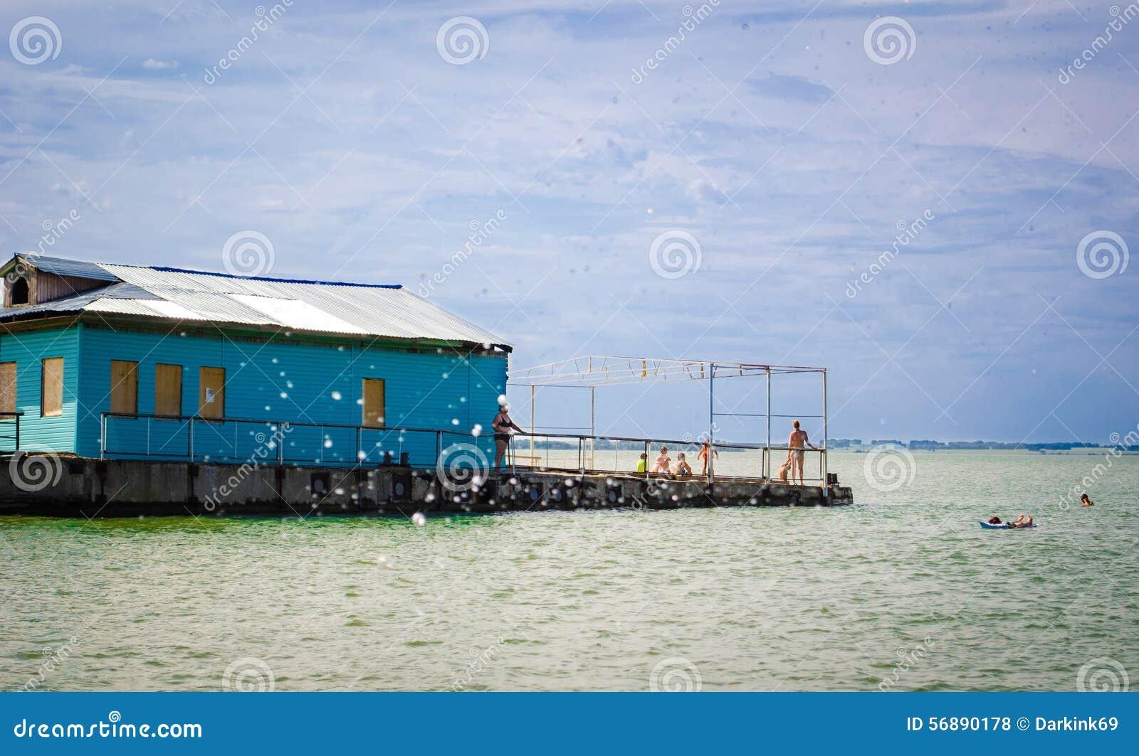 I villeggianti prendono il sole e nuotano alla spiaggia al vecchio pilastro