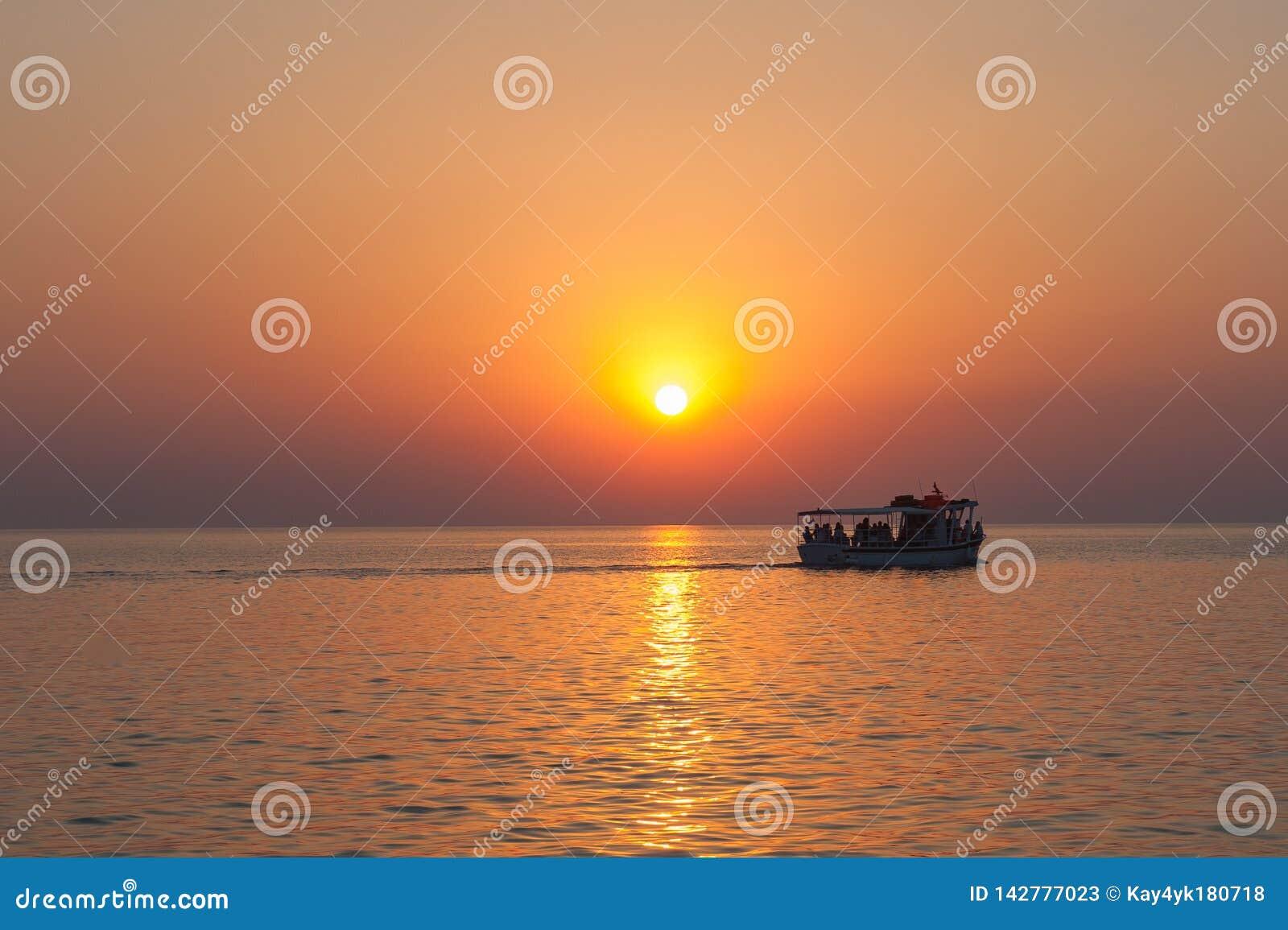 Iate, barco, barco no horizonte e a silhueta de um por do sol bonito, por do sol quente Costela Luminosa do navio de cruzeiros