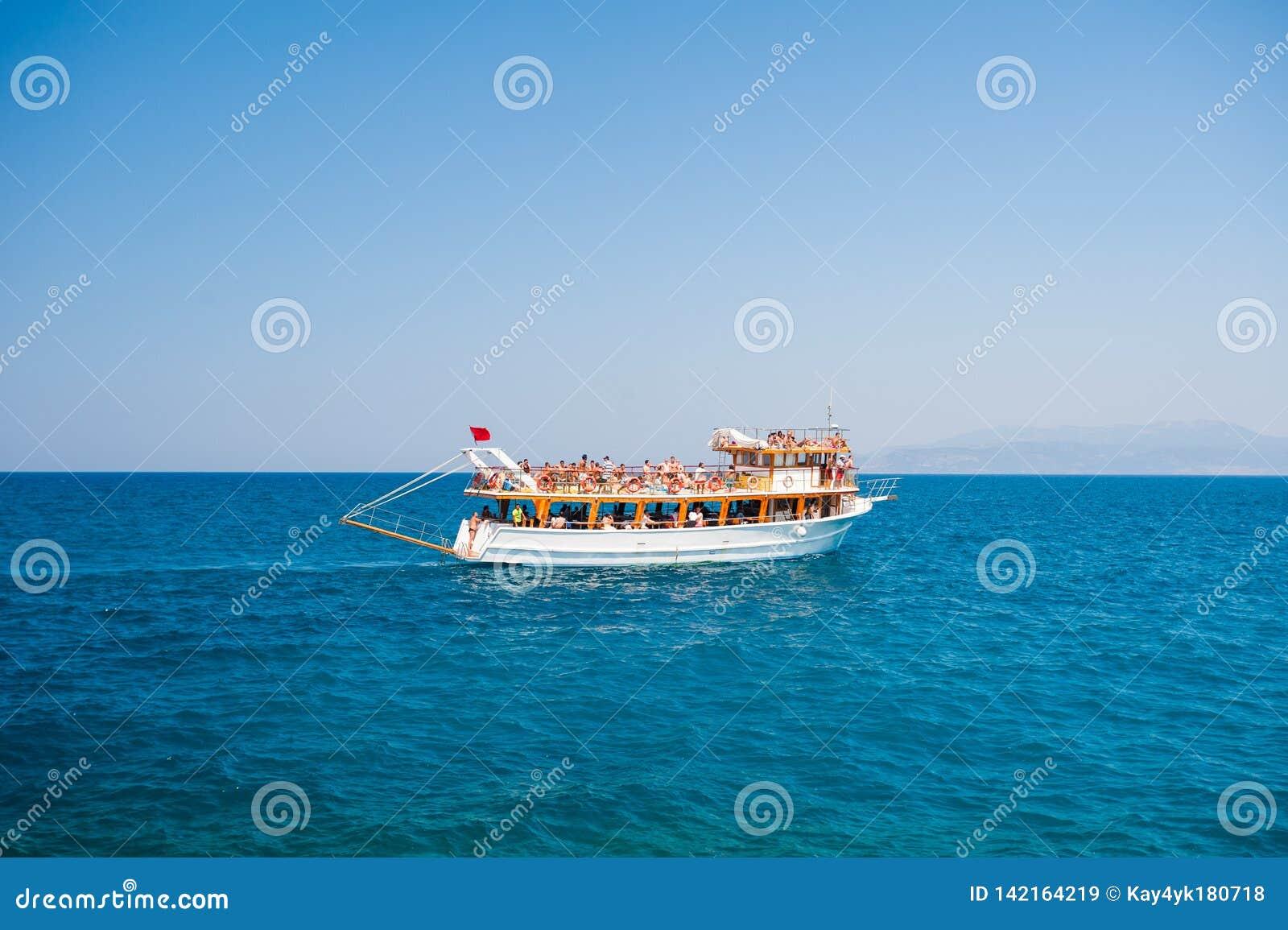 Iate com os turistas que navegam no mar, resto para toda a família, cruzeiro nas ilhas
