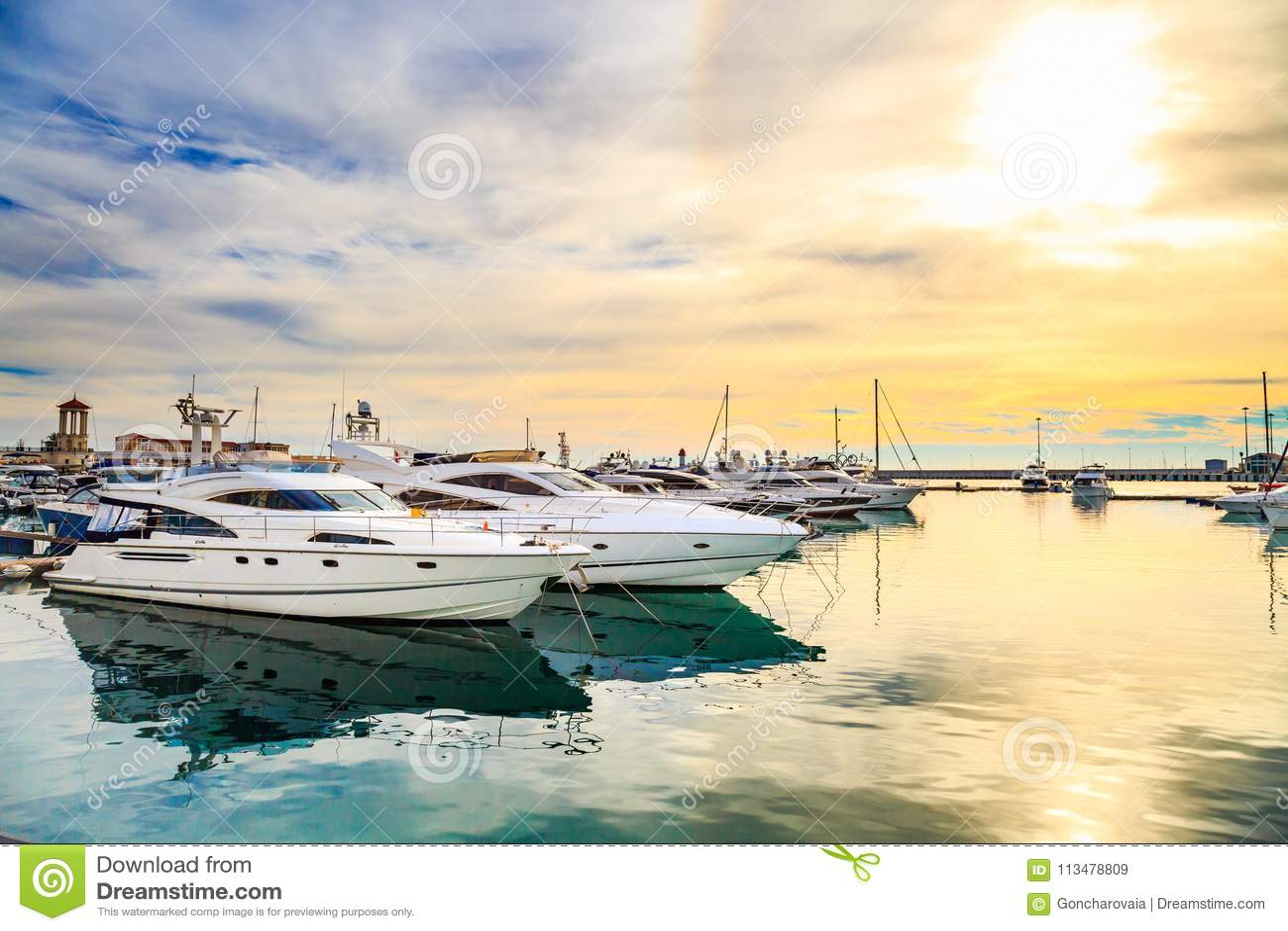 Iate luxuosos no por do sol Doca marinha do motor e de barcos de navigação modernos na luz do sol, mar da água azul, arco-íris co