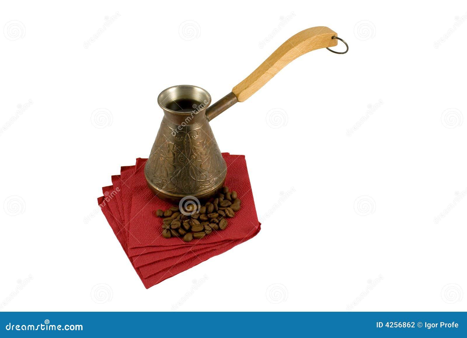 Ibrik avec du café sur une serviette avec des grains de café