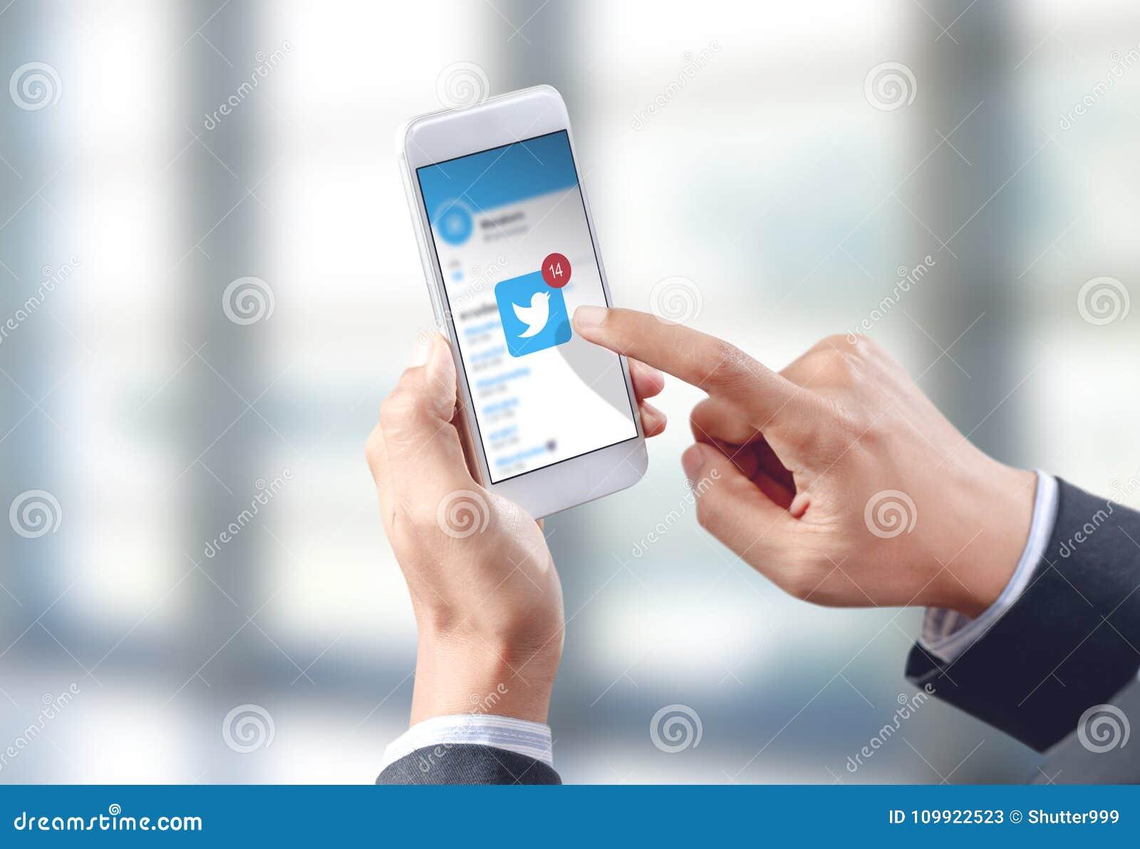Icône de Twitter de contact de main d homme d affaires sur l écran mobile