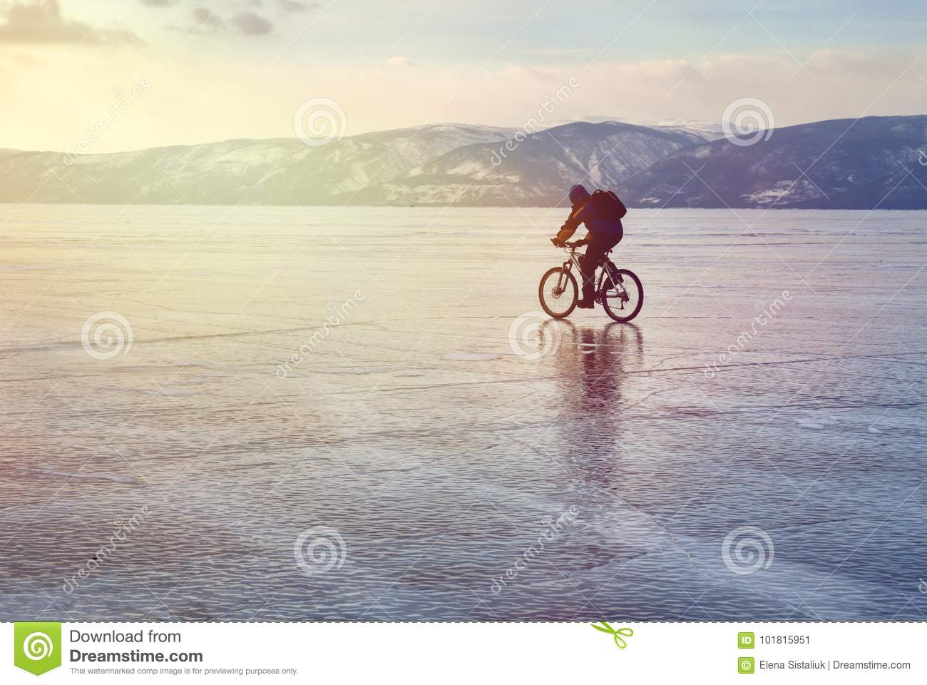 Ice biker traveler with backpacks on bike on ice of Lake Baikal. Against the background of sunset sky, ice surface. Winter sport