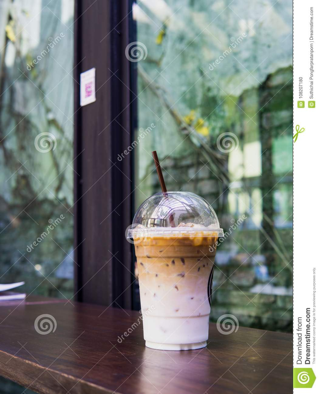 Ice coffee latte in takeaway cup on wood table. Takeaway ice latte in plastic cup with straw on wood table. Cafe shop background w