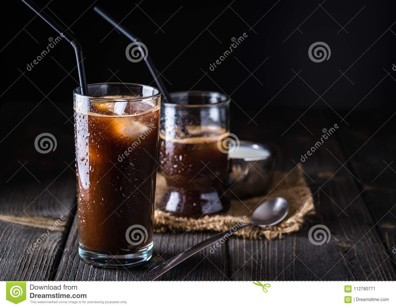 Ice coffee in a tall glass on dark natural desk.