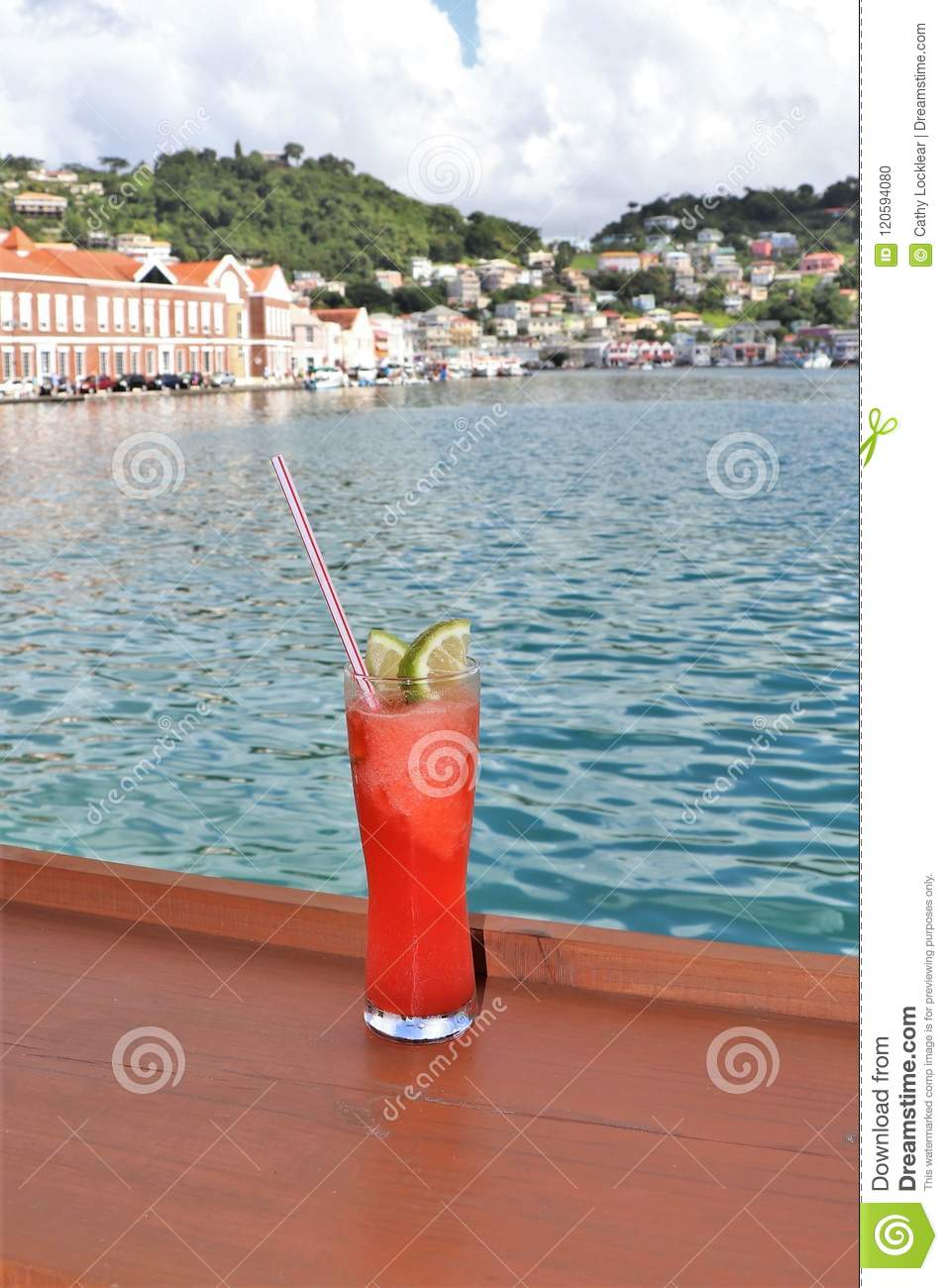 Ice cold drink on a rail with ocean and tropical island scenes in the background