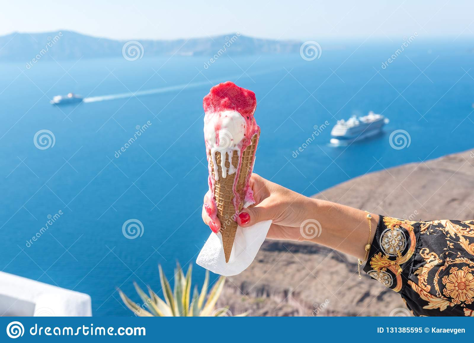 Ice cream in a waffle cone in woman`s hand on background of Santorini island and Caldera in Aegean sea.