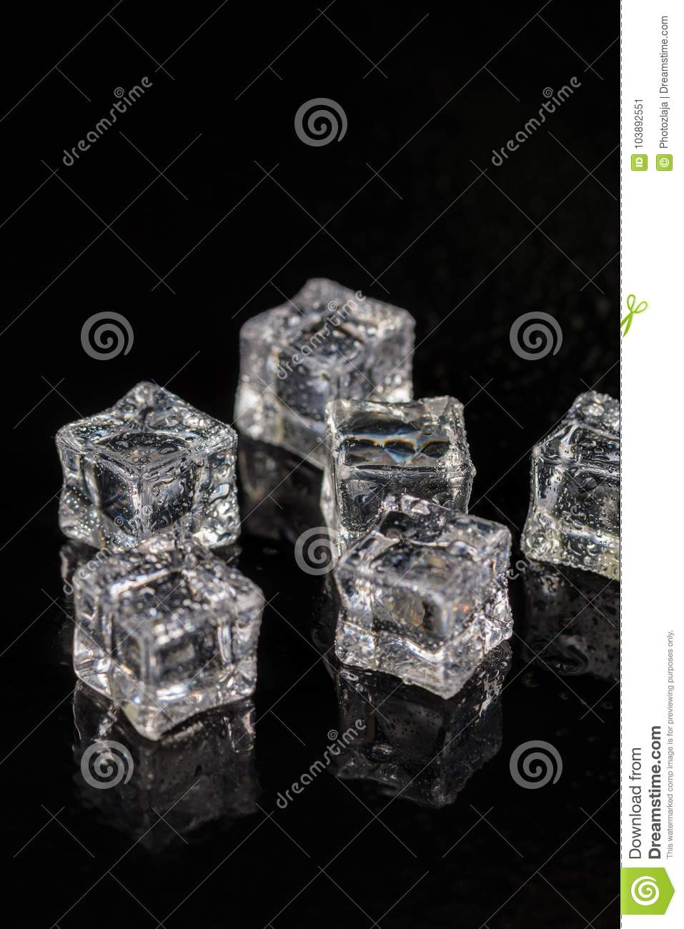 Ice cubes with drops of water on the black background with reflections