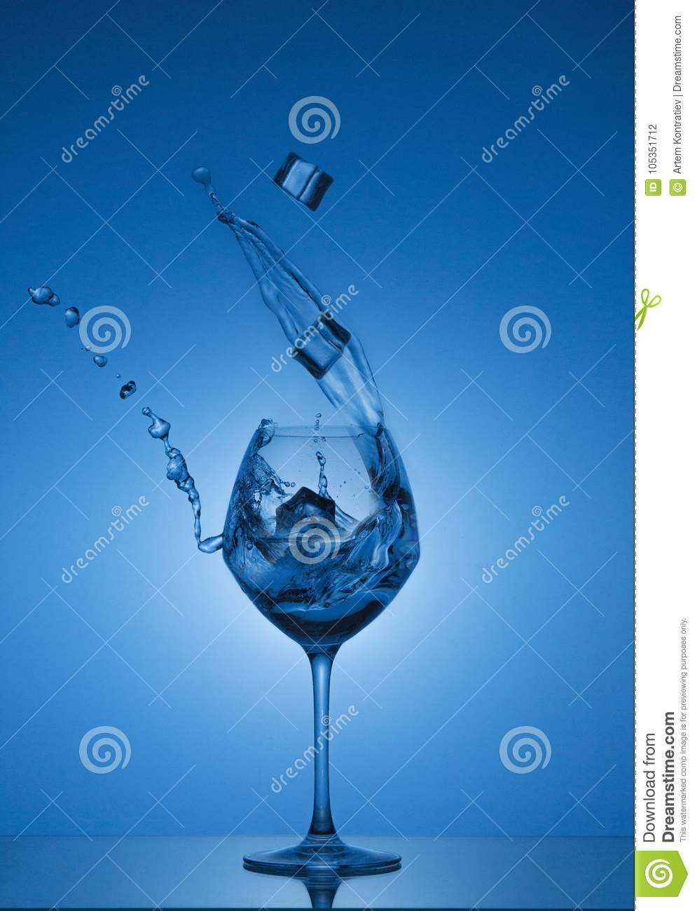 Ice cubes fall into a glass and water is poured out. Water splashing out of a tall wine glass.