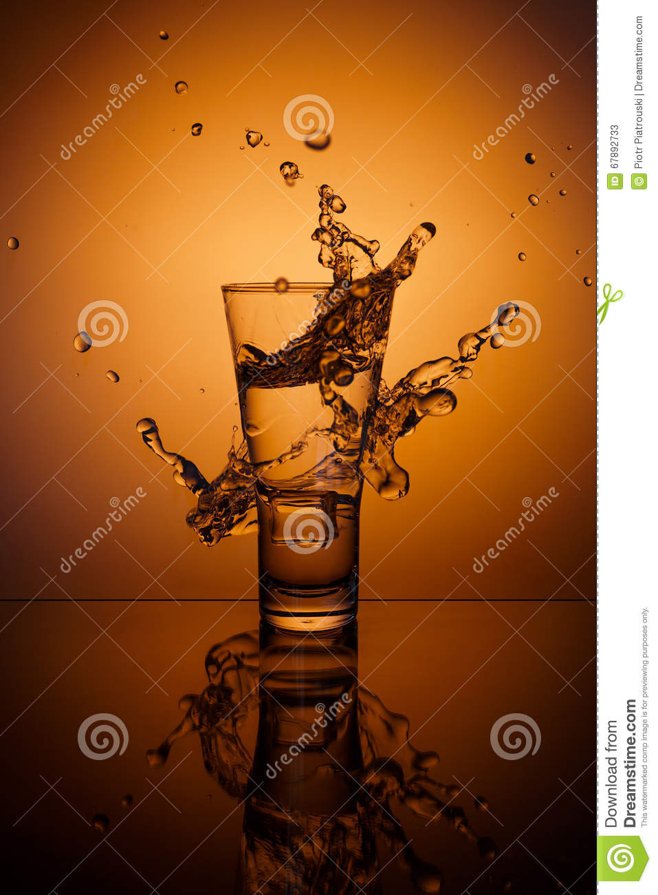 Ice cubes splashing into glass of water