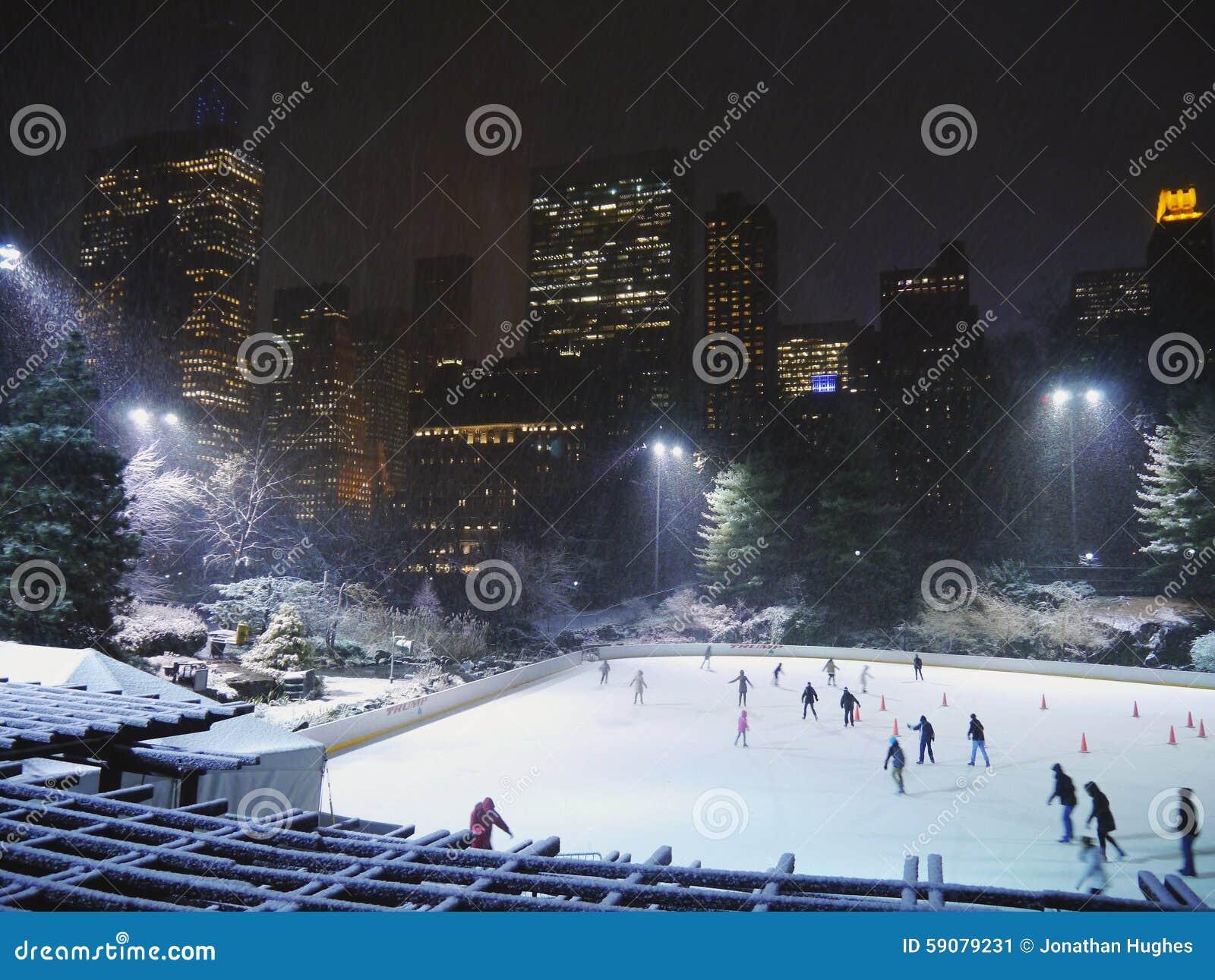 Ice skaters enjoy a wintery central park under snow, NYC