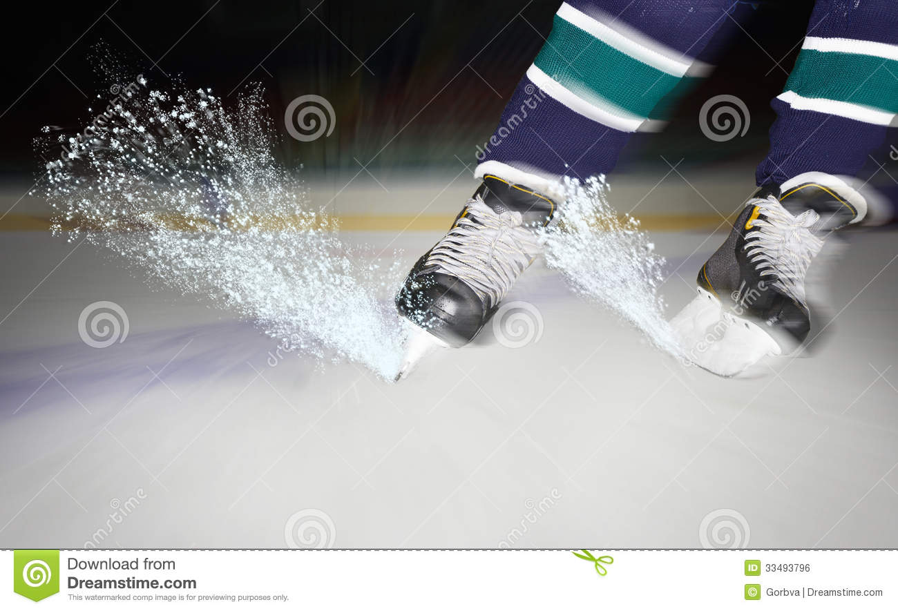Hockey player make ice sparkles on high speed braking. Motion blur ...