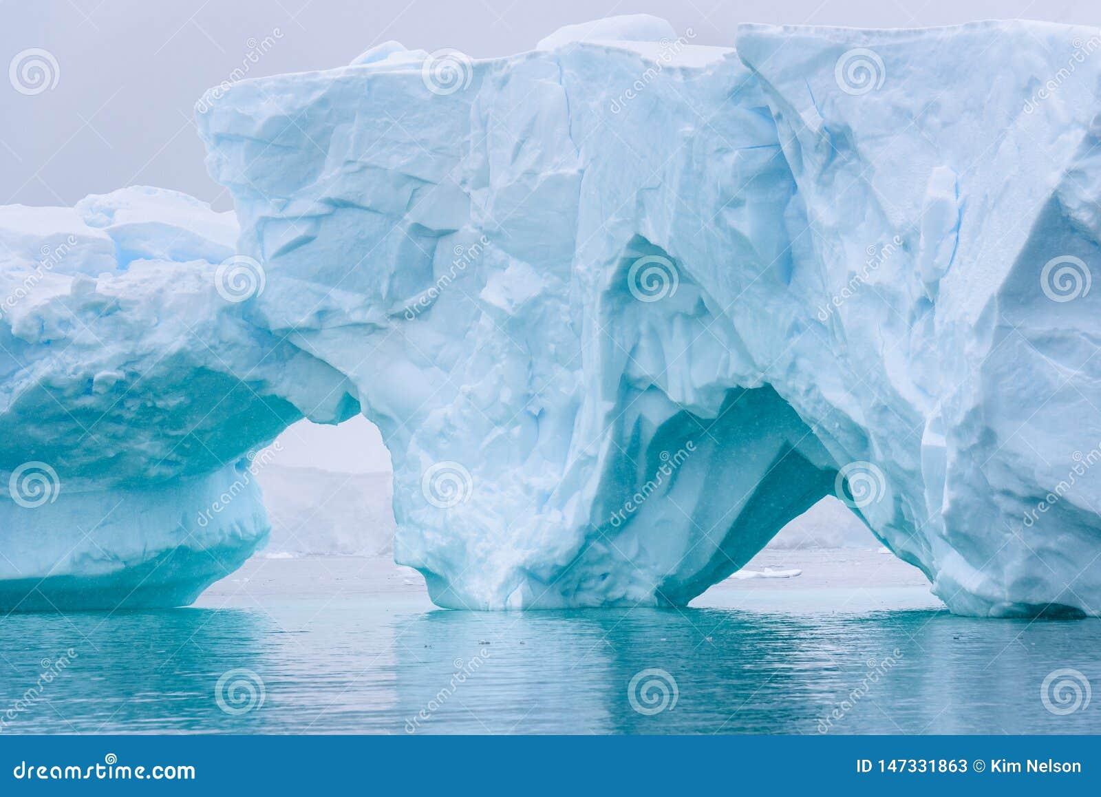 Iceberg bonito do azul de turquesa que flutua no ant?rtico, contra um fundo nevoento
