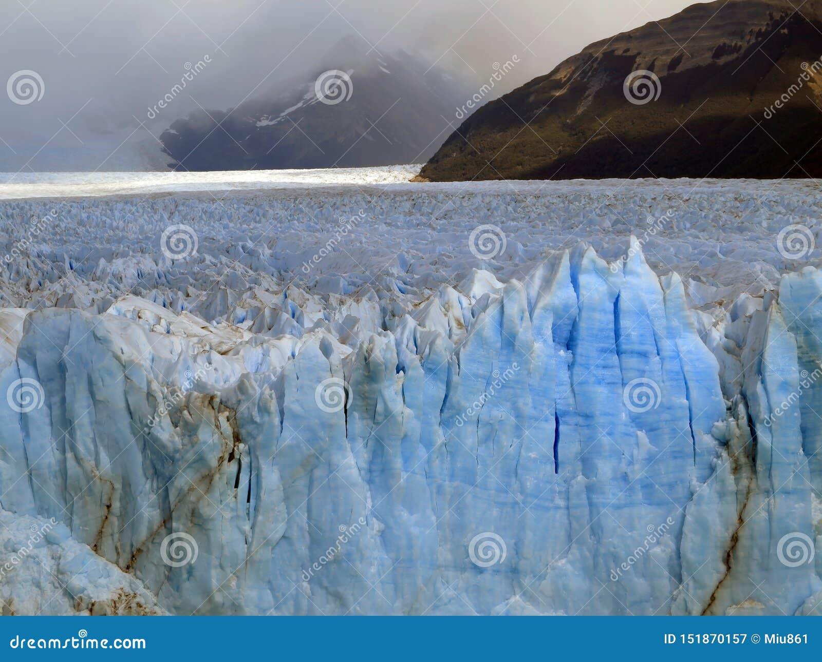 Iceberg Geleira ?rtica A parede do gelo azul Montanhas nevoentas no fundo
