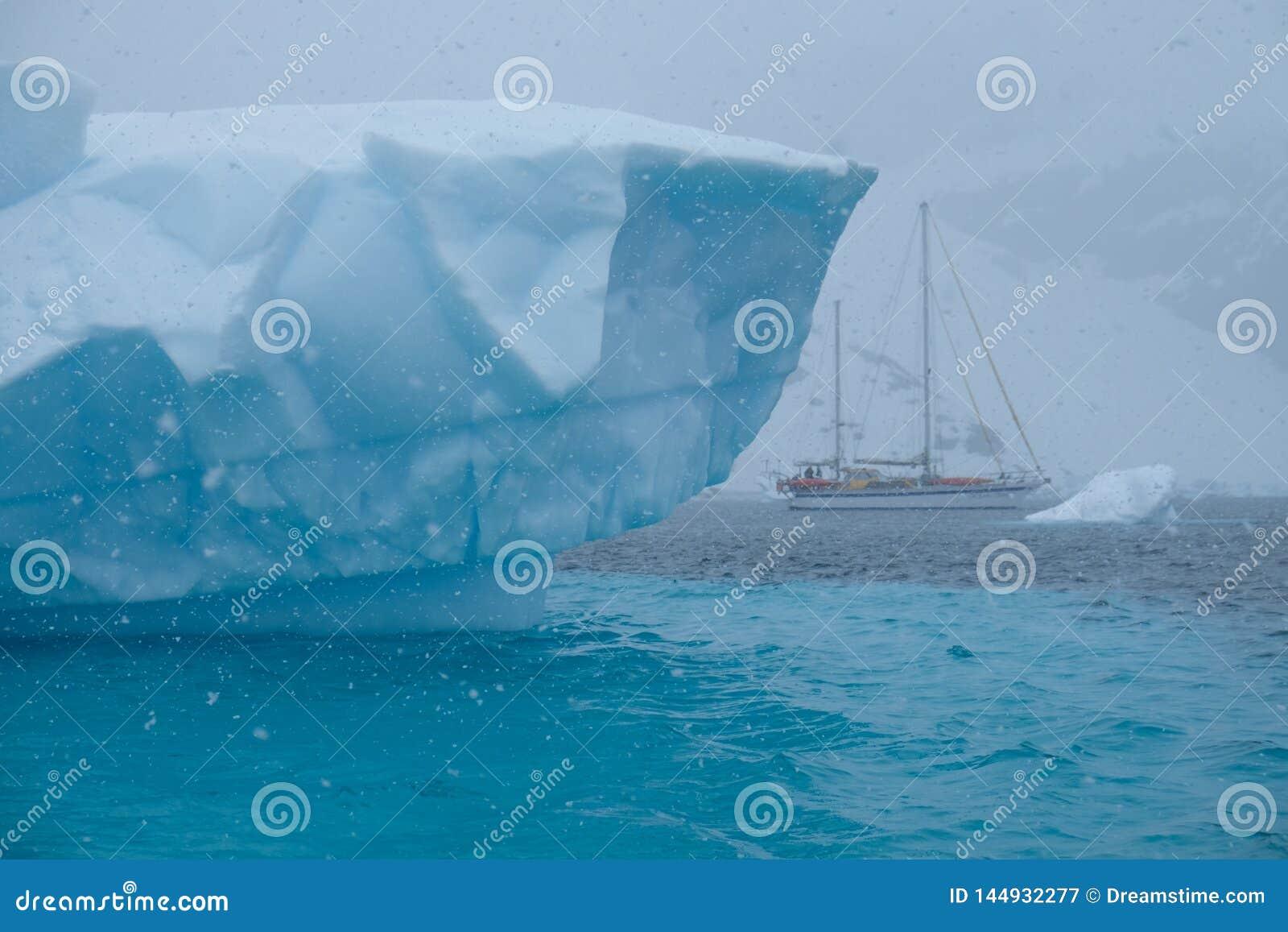 Iceberg listado azul irregular original da Antártica com veleiro