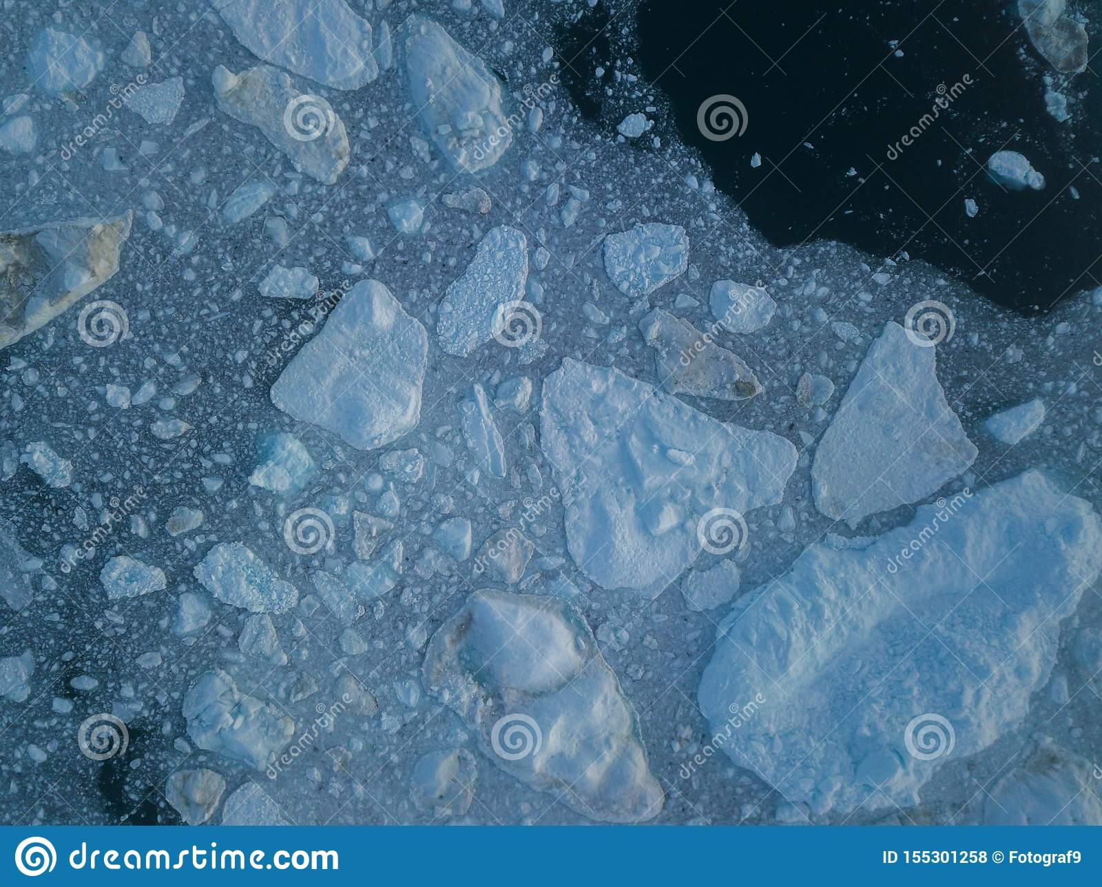 Icebergs drone aerial image top view - Climate Change and Global Warming. Icebergs from melting glacier in icefjord in Ilulissat.