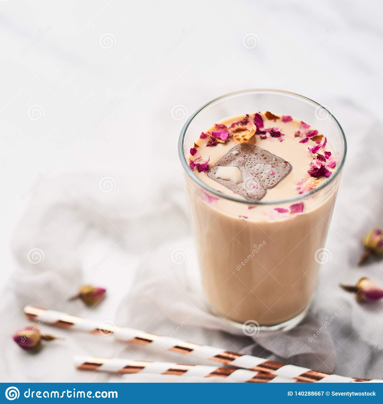 Iced coffee with rose and cardamom in a tall glass