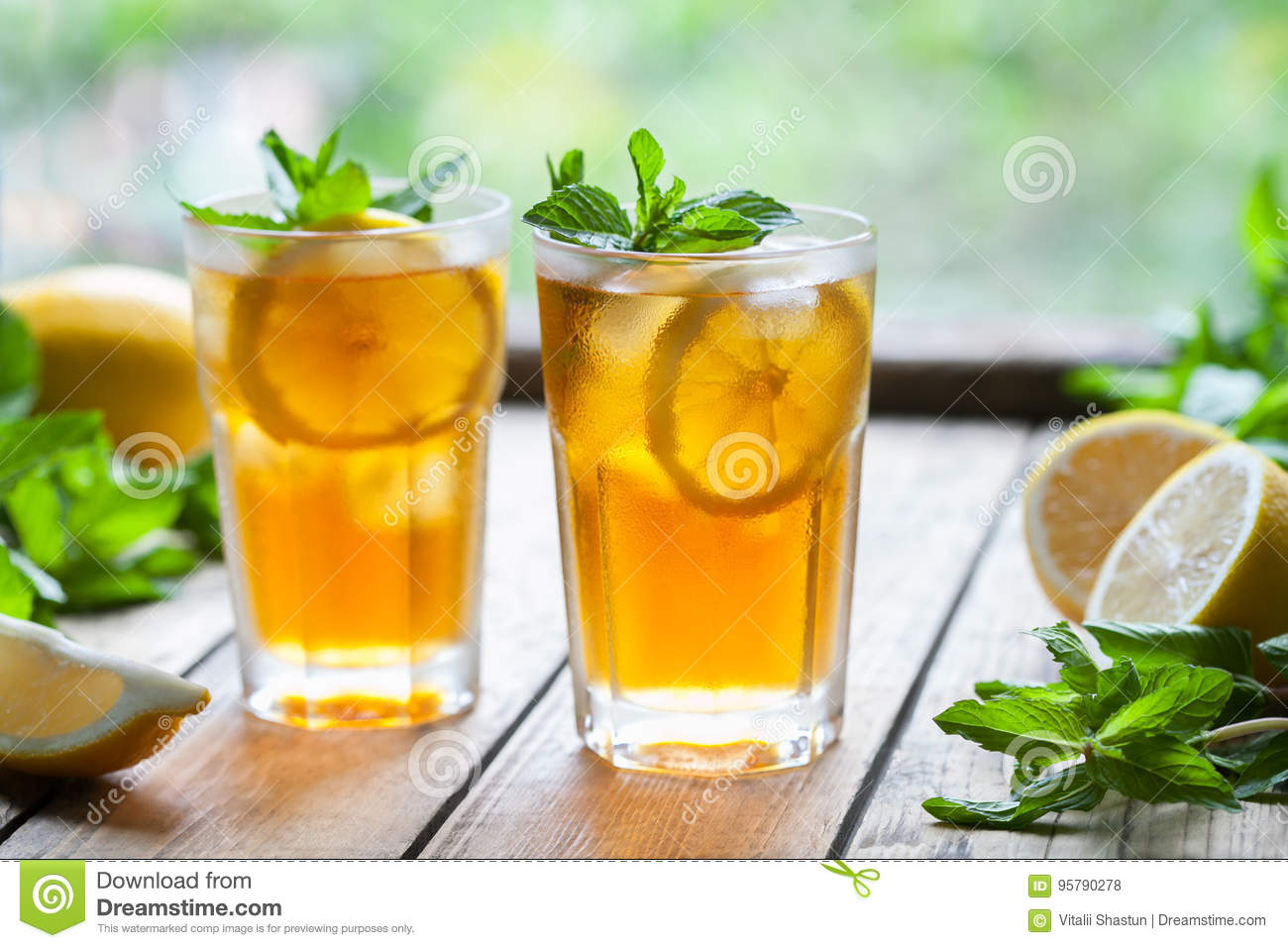 Iced tea with lemon slices and mint on wooden table with a view to the terrace and trees. Close up summer beverage