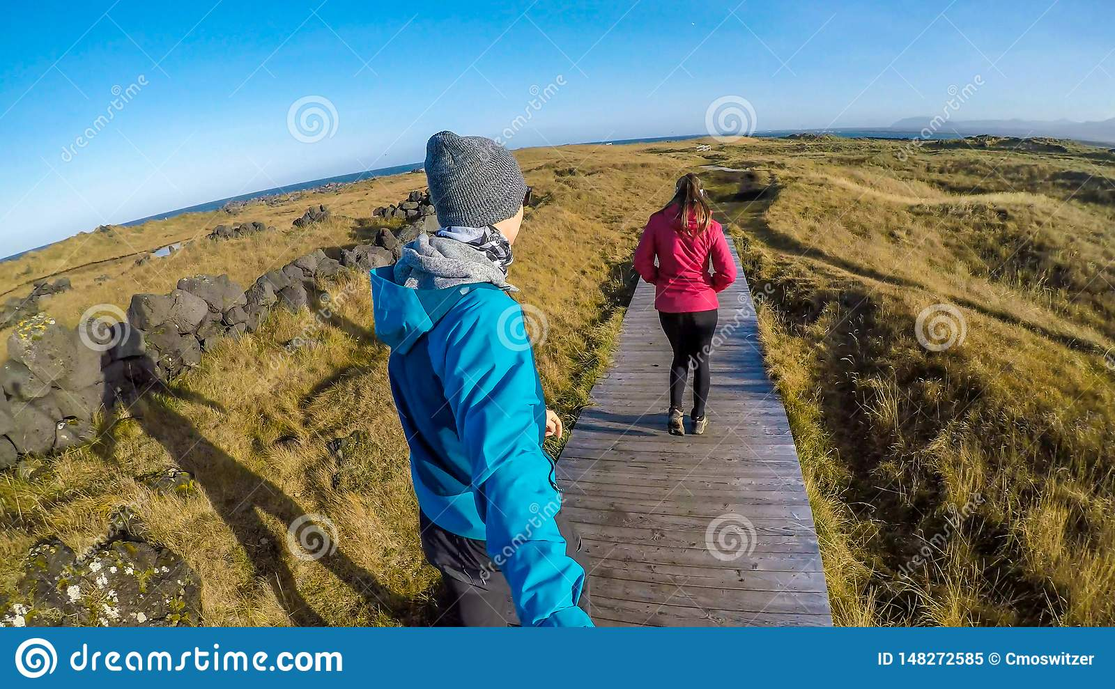 Iceland - A couple walking on a path across the grassland