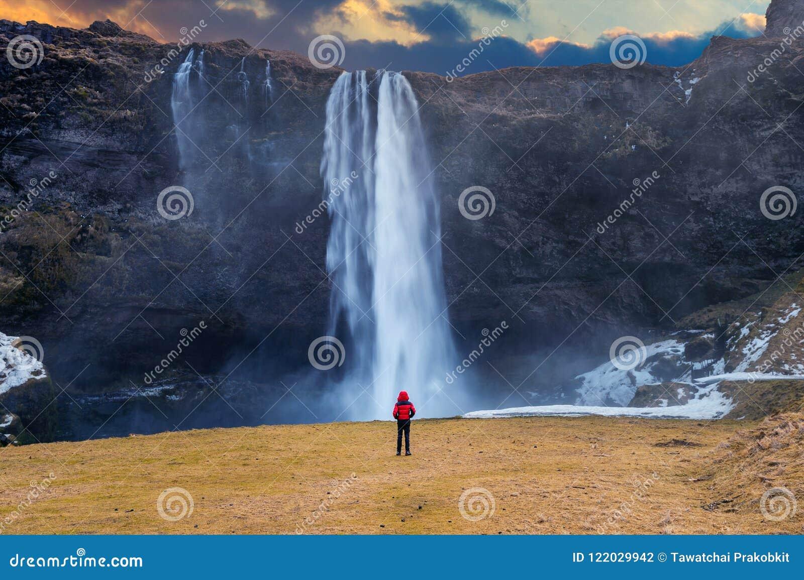 Iceland seljalandsfossvattenfall Grabben i rött omslag ser den Seljalandsfoss vattenfallet