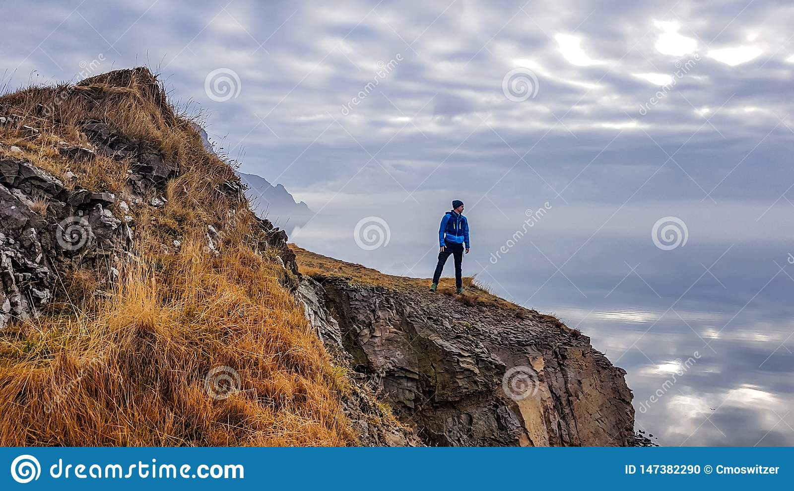 Iceland - Young man standing at the cliff with an endless horizon