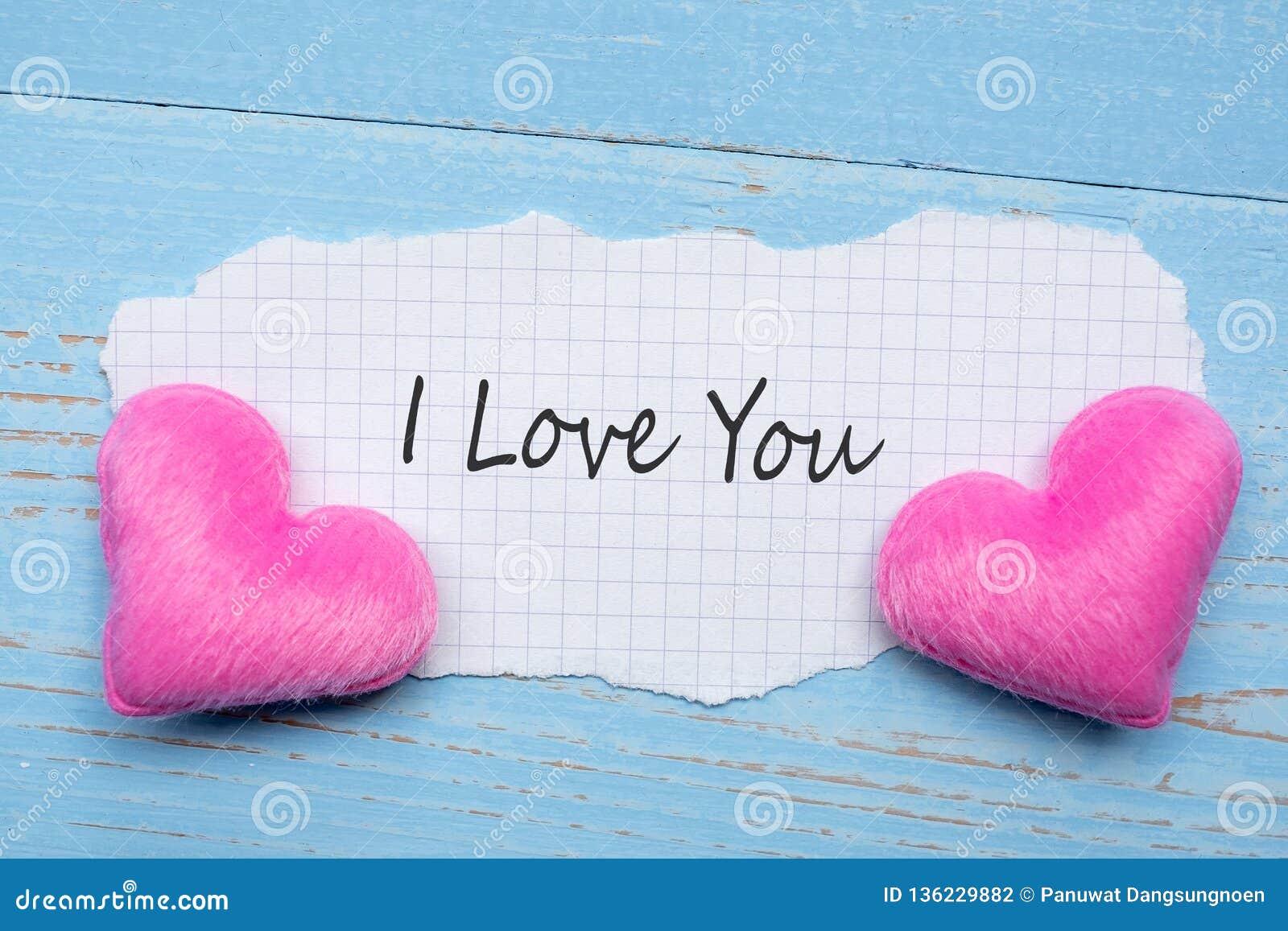 ICH LIEBE DICH Wort auf Papieranmerkung mit Herz-Formdekoration der Paare rosa auf blauem Holztischhintergrund Heirat, romantisch