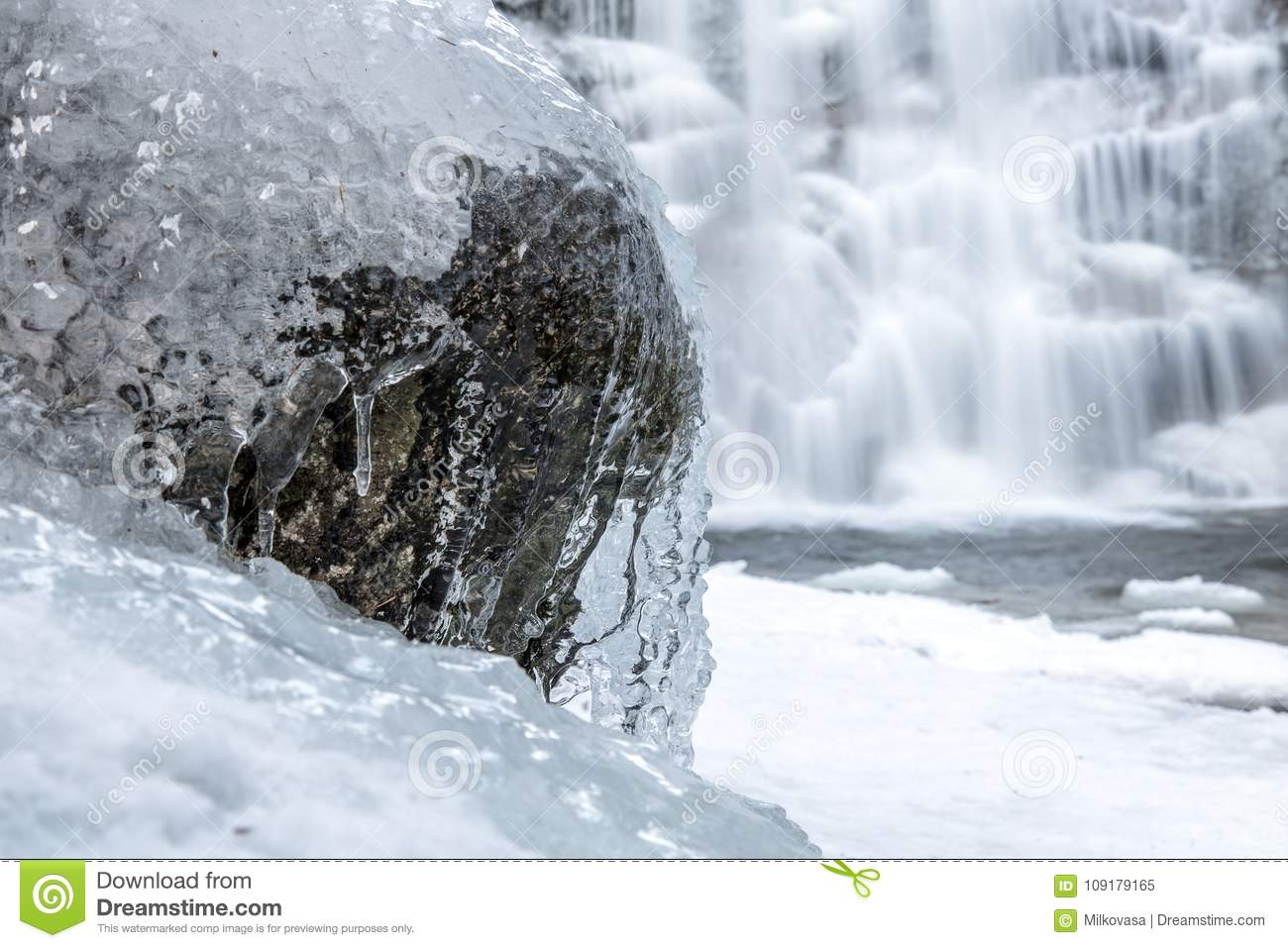 The water stream is froze on the stone