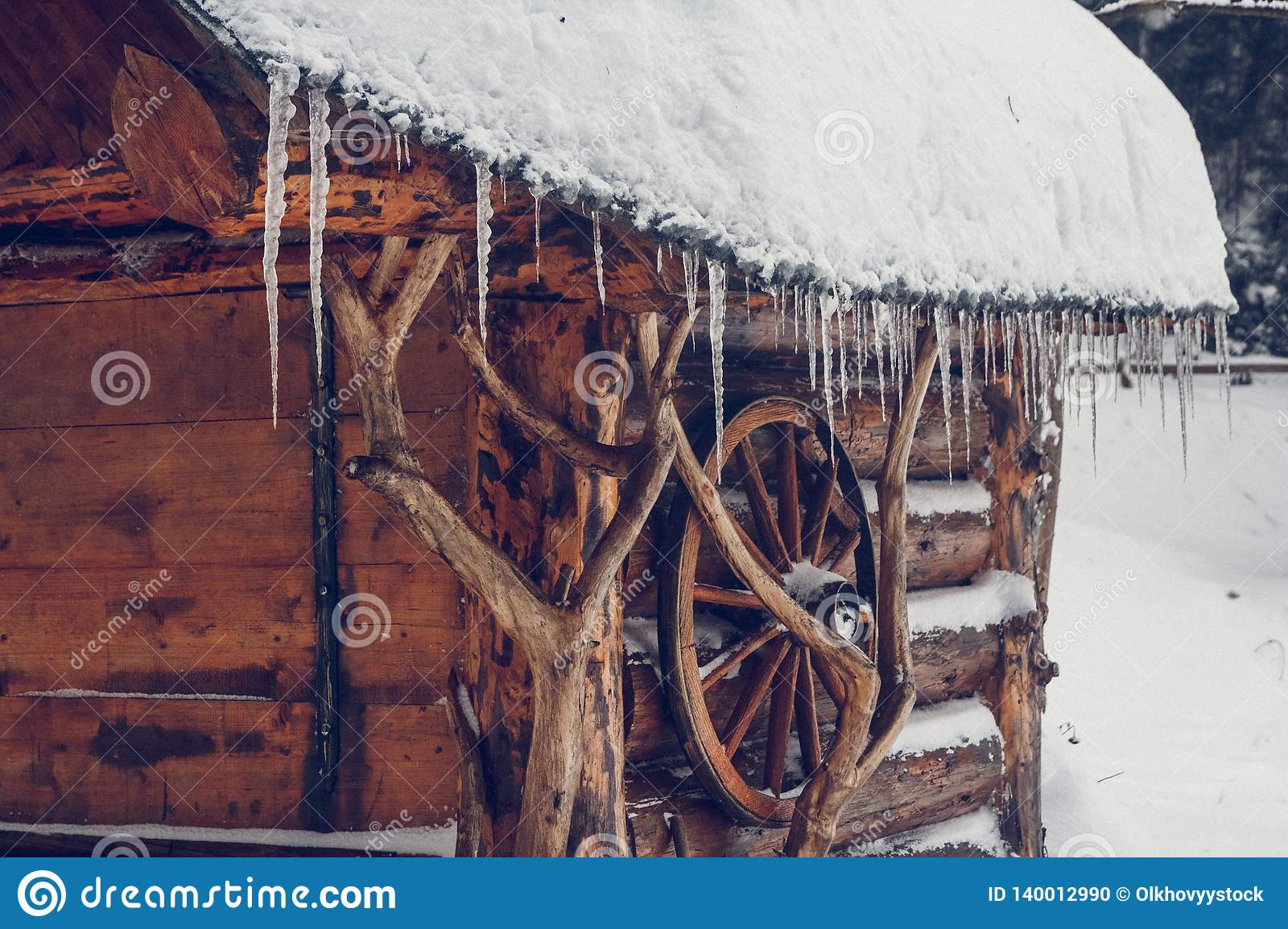 Icicles hang from the roof of a wooden house in the forest near the mountain ash