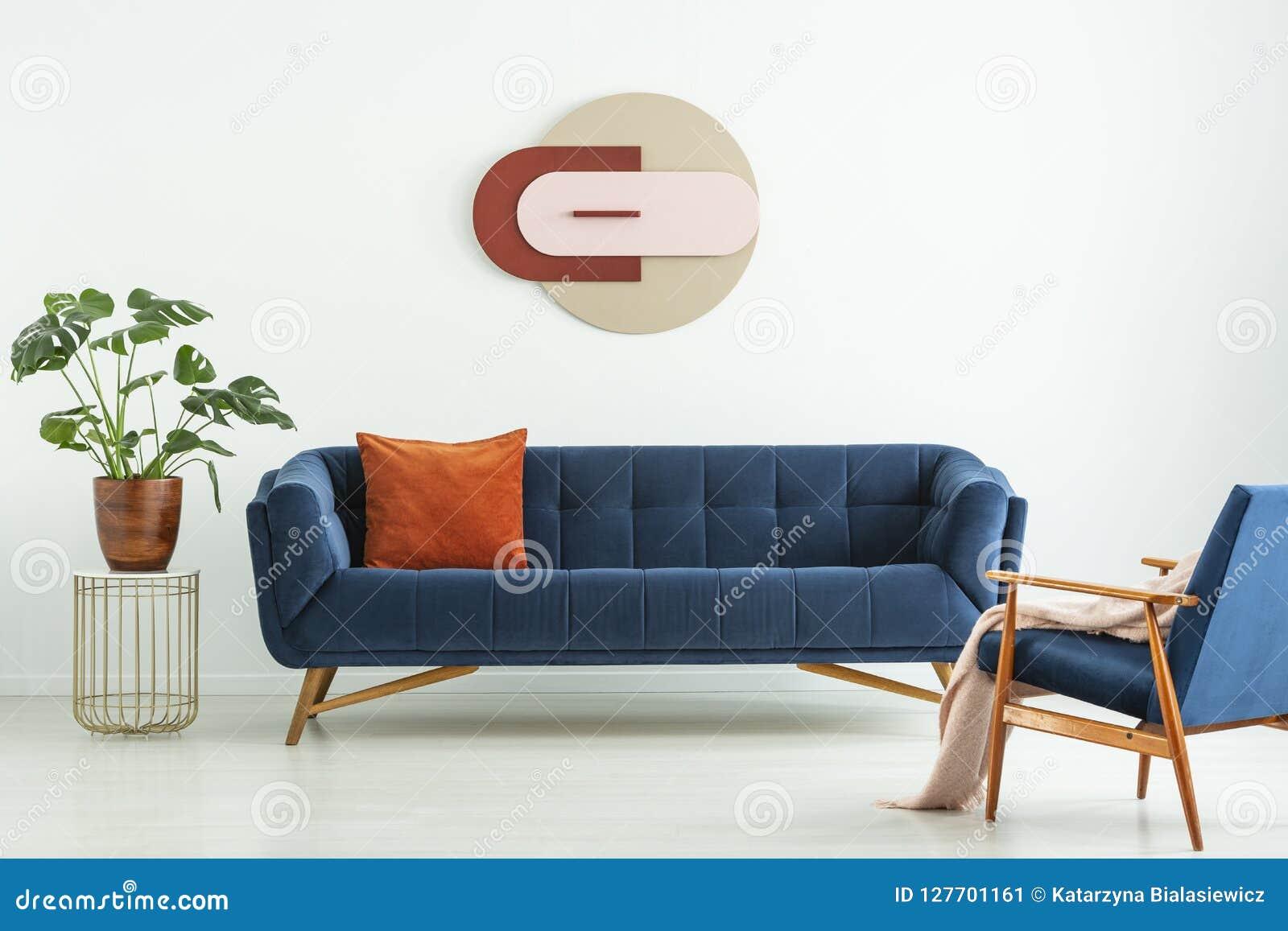 Idérik geometrisk konst på en vit vägg ovanför en elegant blå soffa i inre för mitt--århundrade en modern stilvardagsrum Verkligt