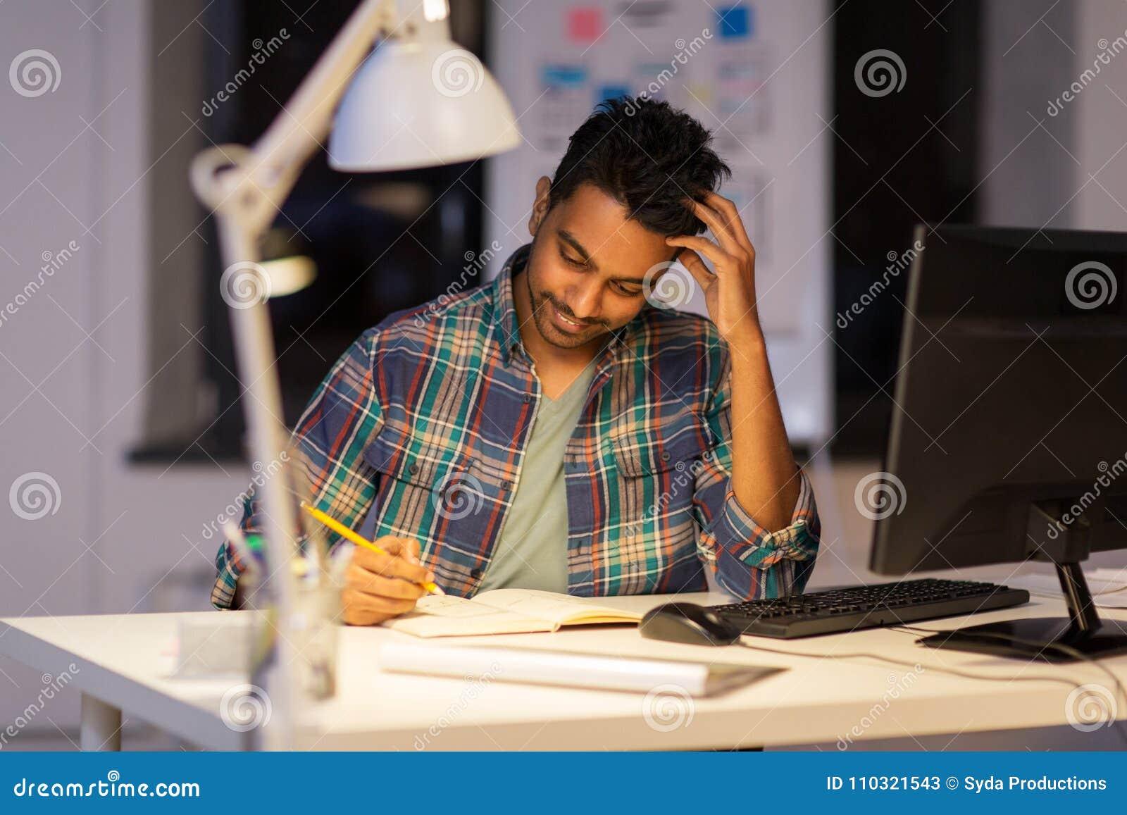 Idérik man med anteckningsboken som arbetar på nattkontoret
