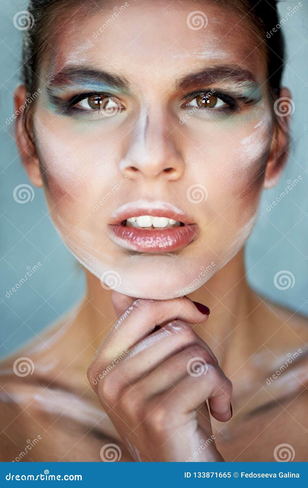 Idérik personlighet med makeup, målarfärgsudd på framsidan Håller hans hand under hans haka Idérik personlighet, sökande