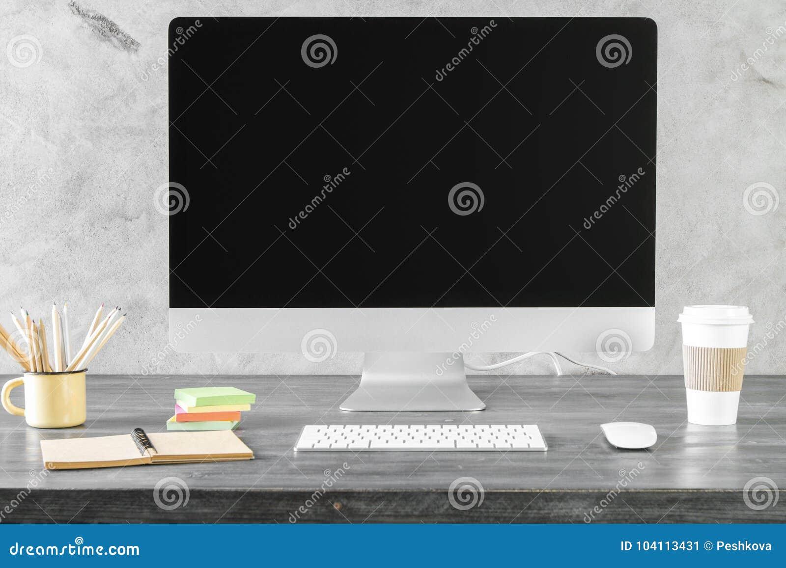 Idérikt skrivbord med den rena datorskärmen