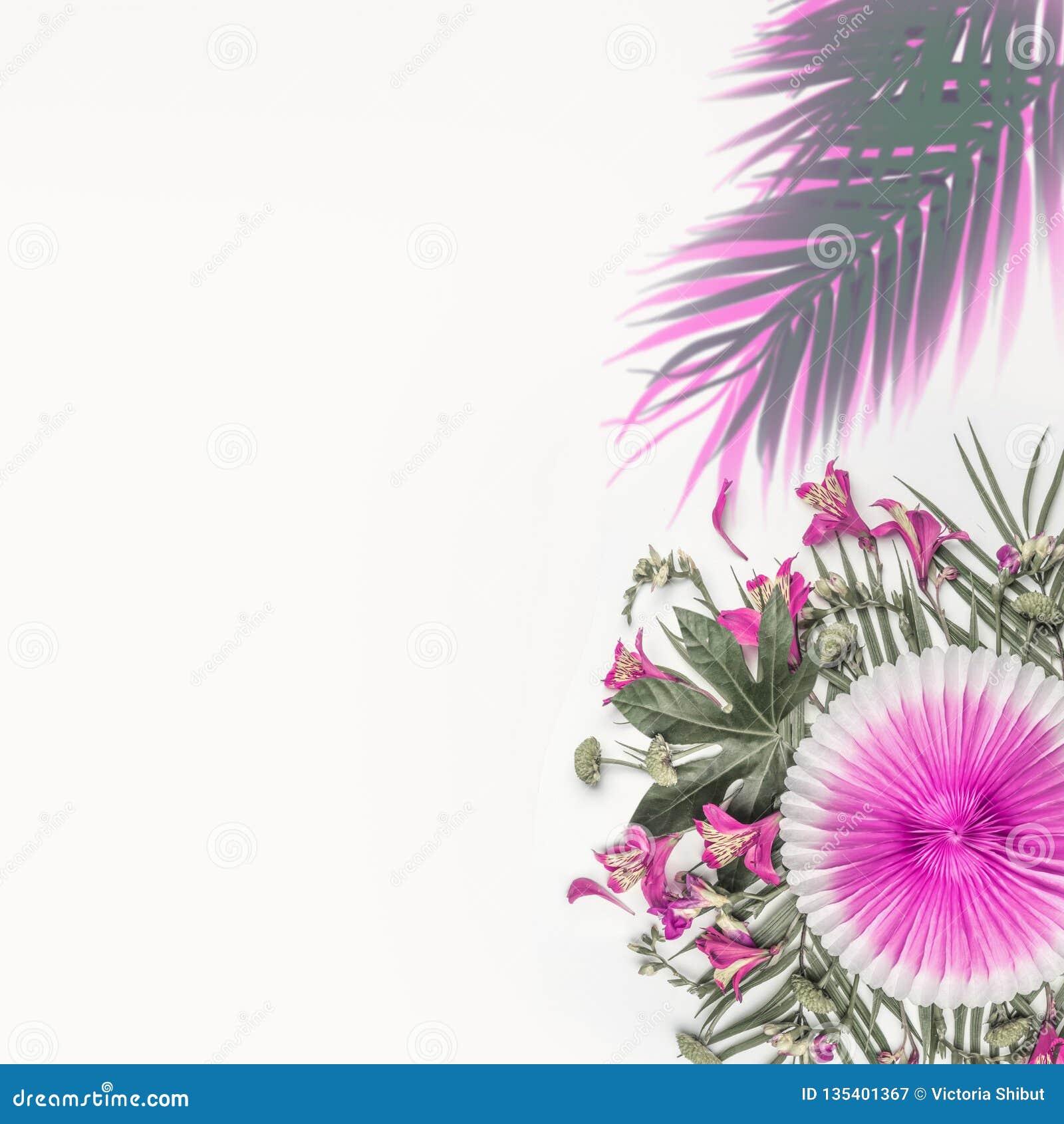 Idérikt tropiskt komponera med exotiska blommor, palmblad och den rosa partipappersfanen på vit bakgrund, bästa sikt blom- round