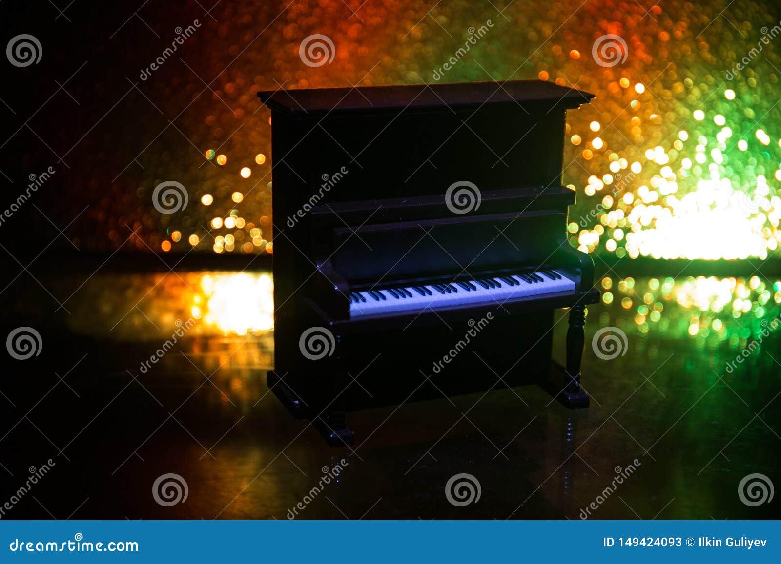Id?rikt begrepp Konstverkgarnering med pianot p? m?rk tonad dimmig bakgrund med ljus