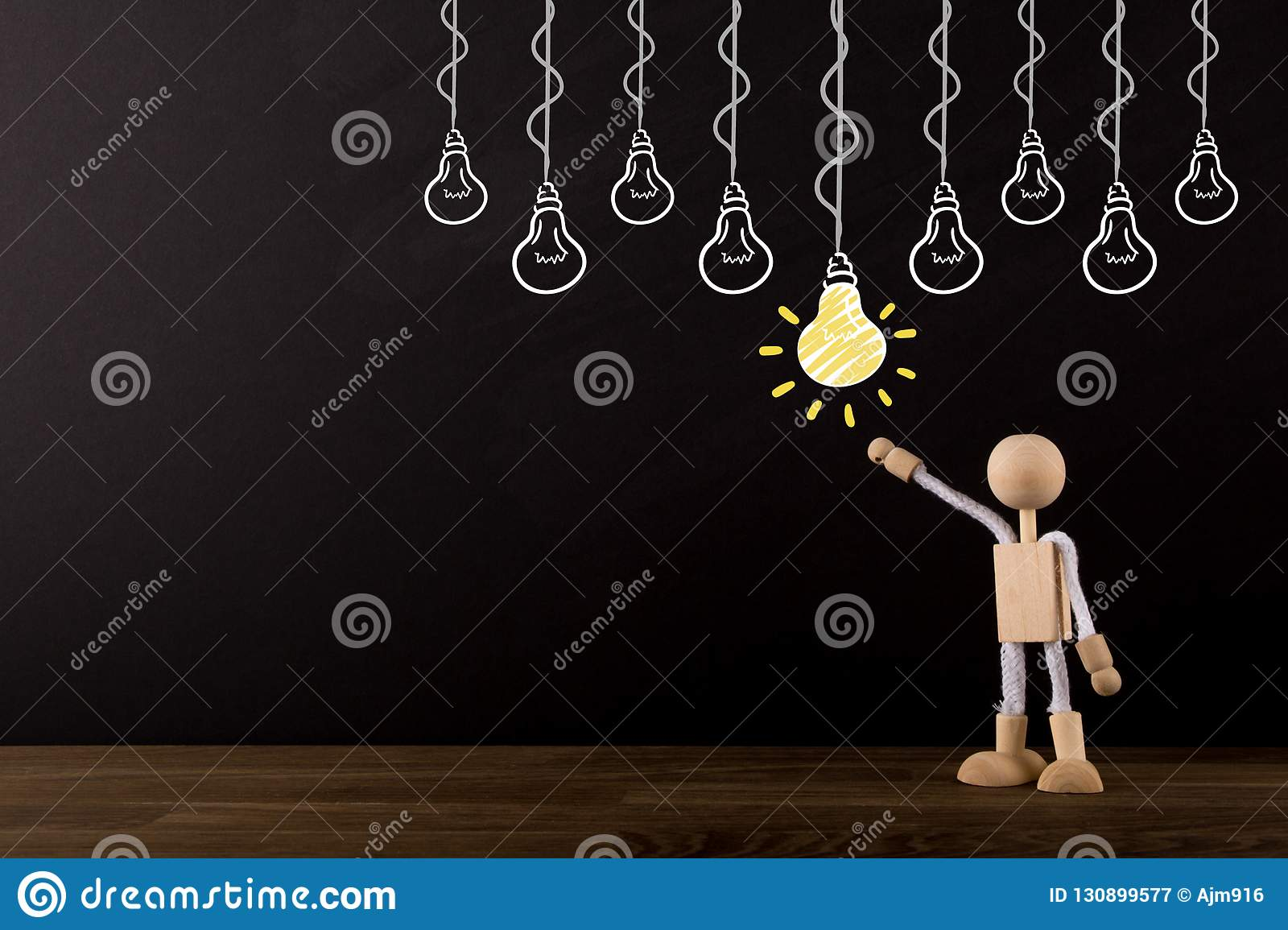 Idea concept, choosing the best idea, Brainstorming, Innovative Wooden Stick Figure pointing at a yellow light bulb